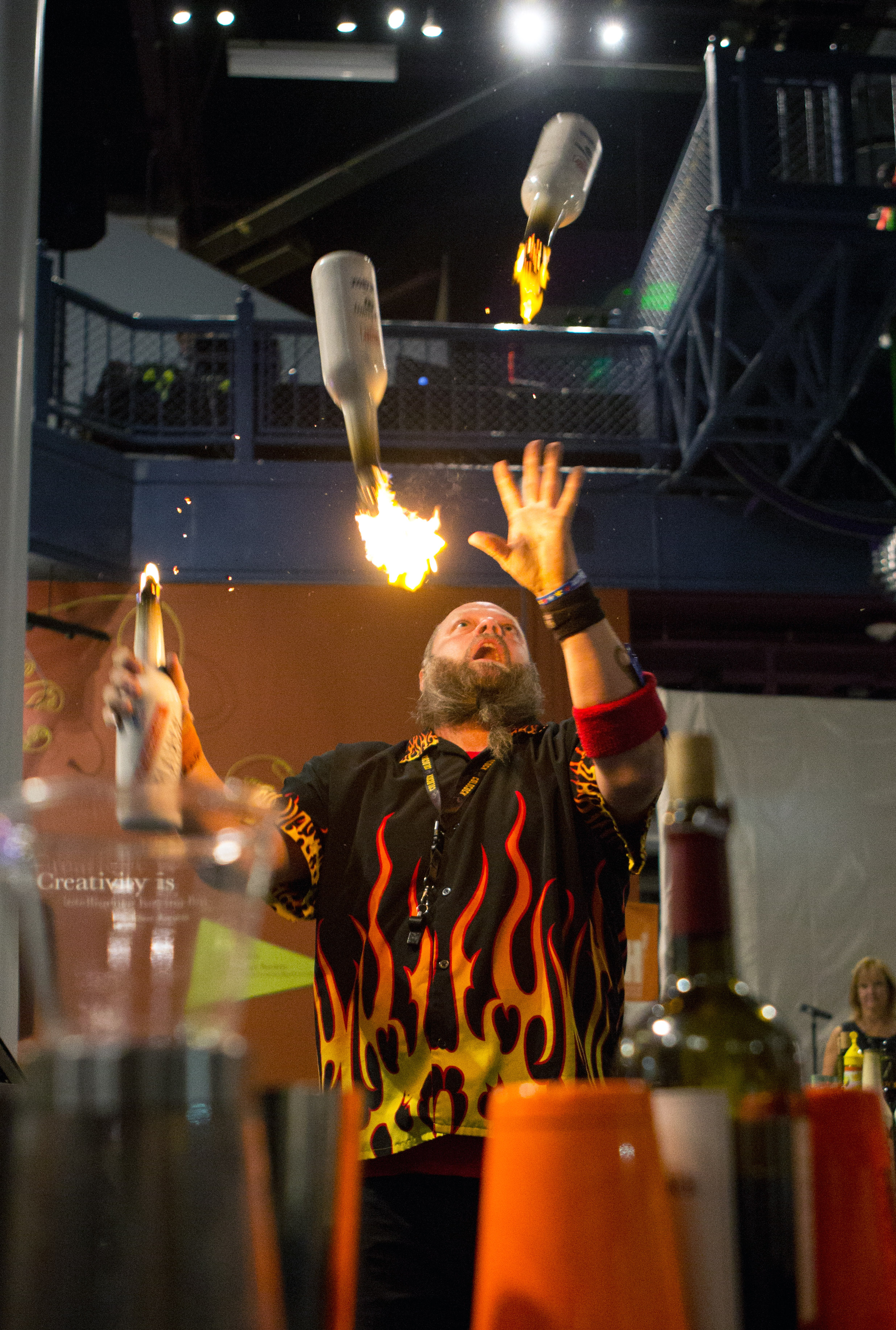 Celebrity mixologist Robbie Flair juggles flaming liquor bottles as part of a flair branding performance during the Bash 7 fundraiser at Imagination Station in downtown Toledo on Saturday, Sept. 17, 2016.
