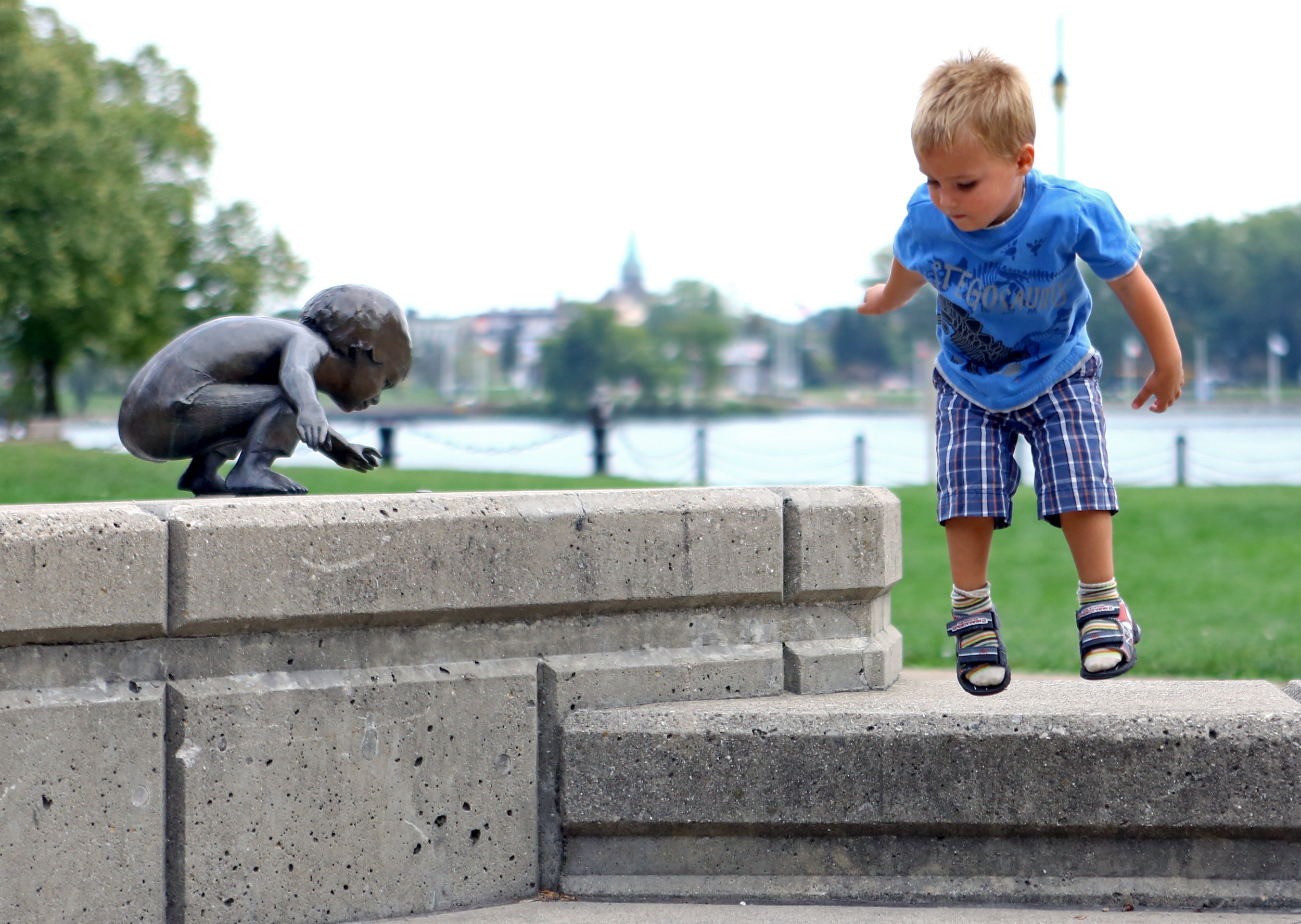 Bowen Brossia, 2, of Toledo jumps from a ledge by the statues in Toledo Park outside of the Imagination Station on Friday, Sept. 23, 2016.