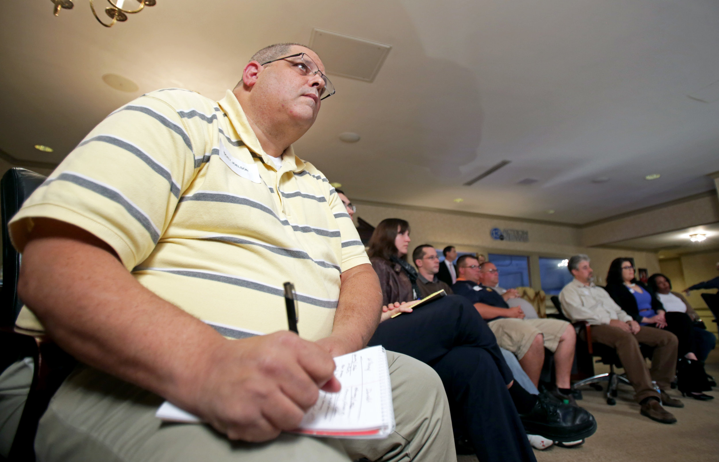 Undecided voter Doev Joelson of Sylvania takes notes on each of the candidates' points during a presidential debate viewing at the WTVG studio in Toledo on Monday, Sept. 26, 2016.
