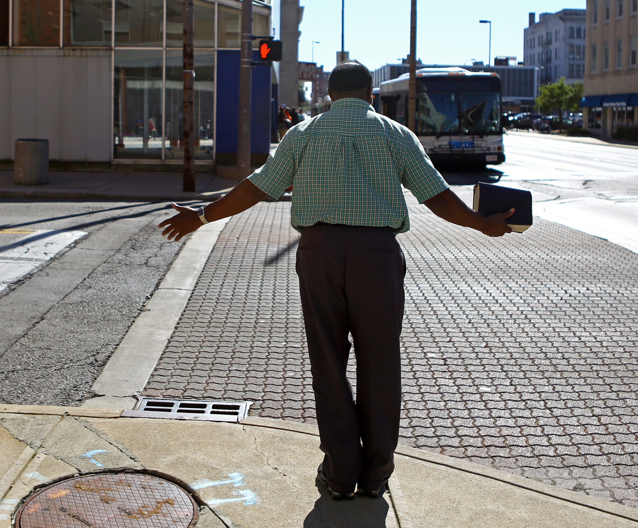 """Brother Gibbs preaches on the corner of Madison Ave. and Erie St. on Tuesday, Sept. 27, 2016. Brother Gibbs tries to preach on this corner at least four times a week and says """"I ain't spreading bad news, I'm spreading good news."""""""