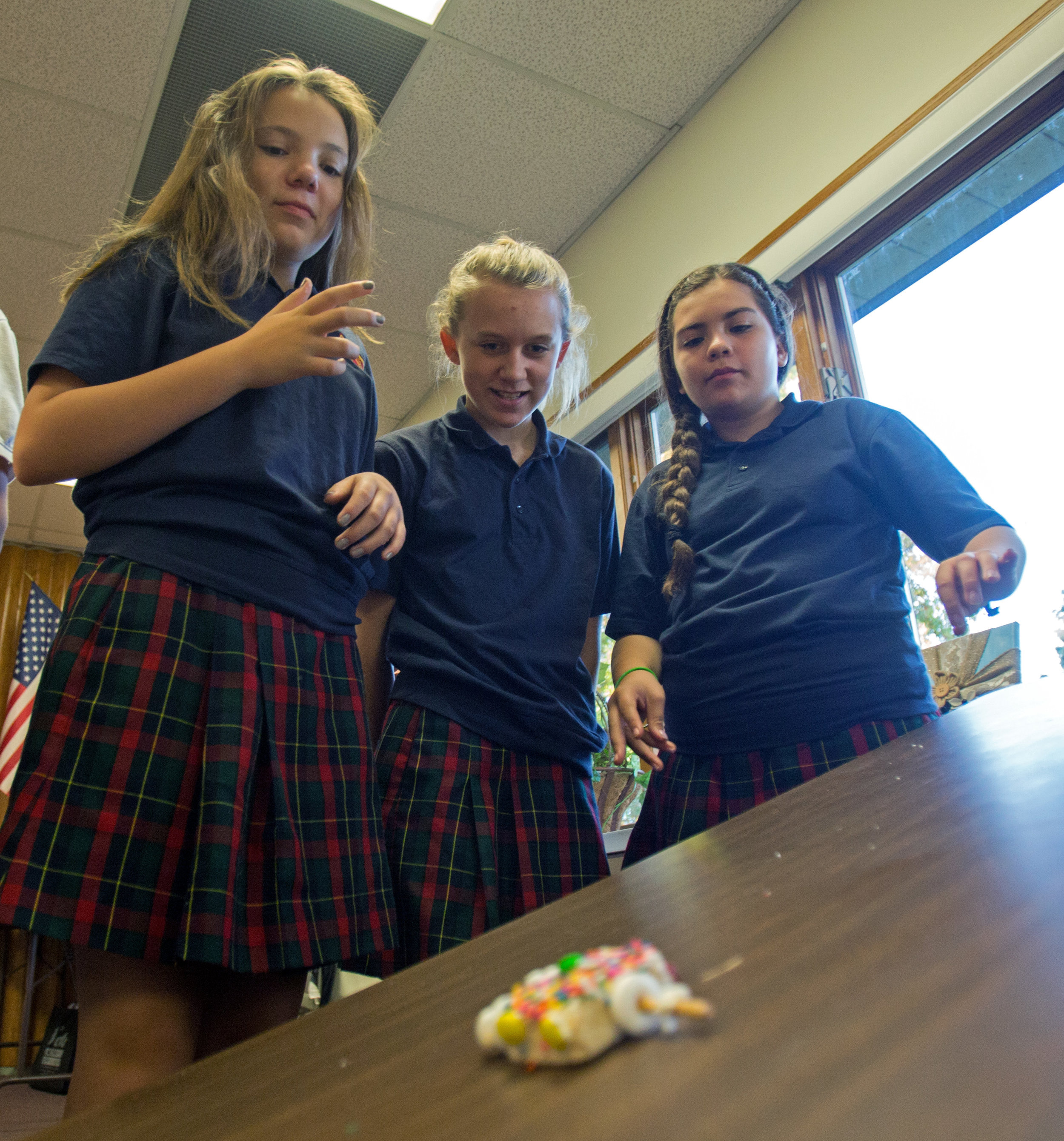 From left to right: Kendall Moesenthin, Ella Isaacs, and Adrisa Clark watch as their edible car built as part of the school's STEAM program slides down a ramp in their classroom at St. Joan of Arc School in Toledo on Wednesday, Oct. 19, 2016.