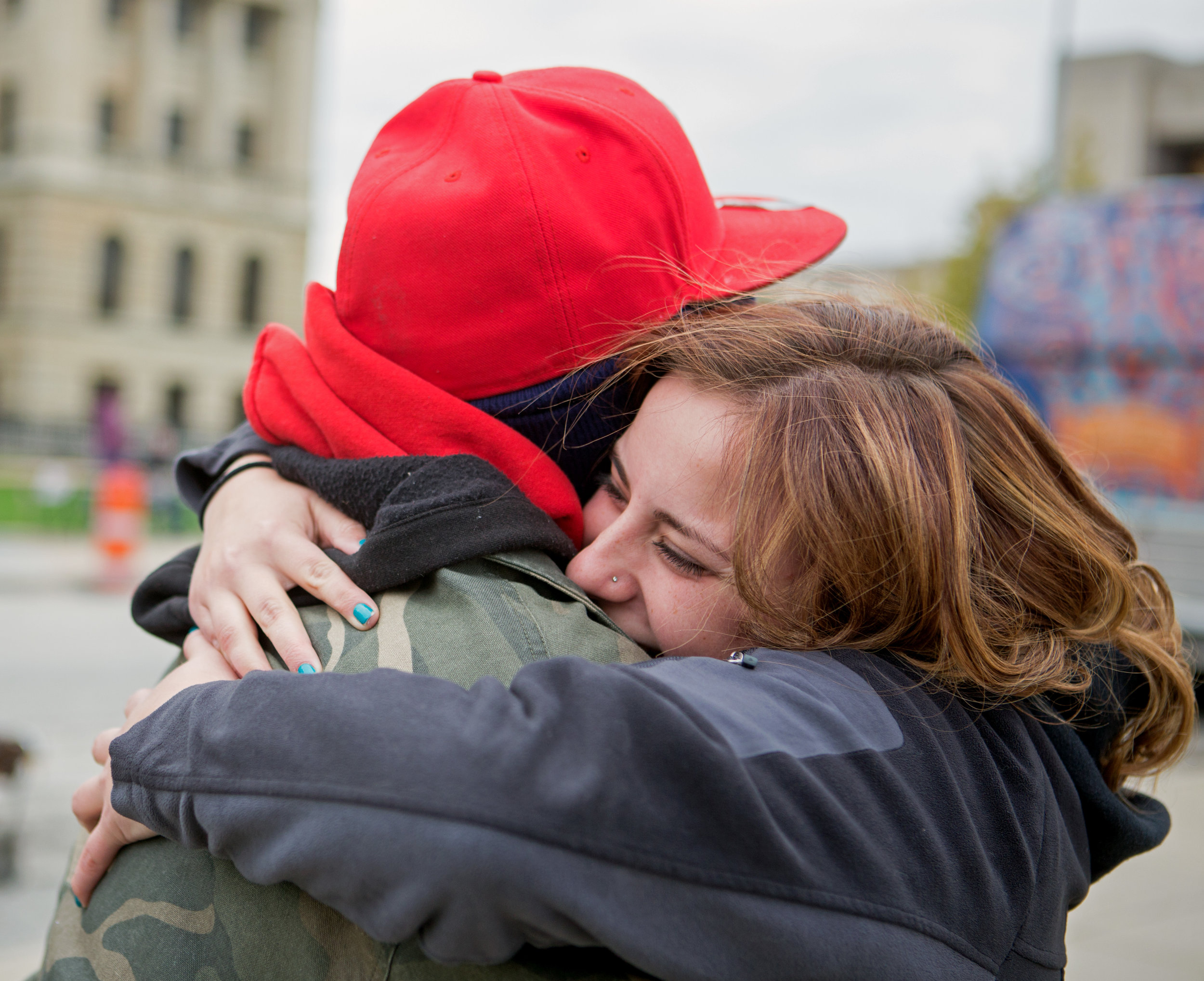 Former Tent City mayor Selena Green hugs clothing tent volunteer Terrance Burch before the start of  Tent City at Civic Center Mall in Downtown Toledo on Friday, Oct. 21, 2016.