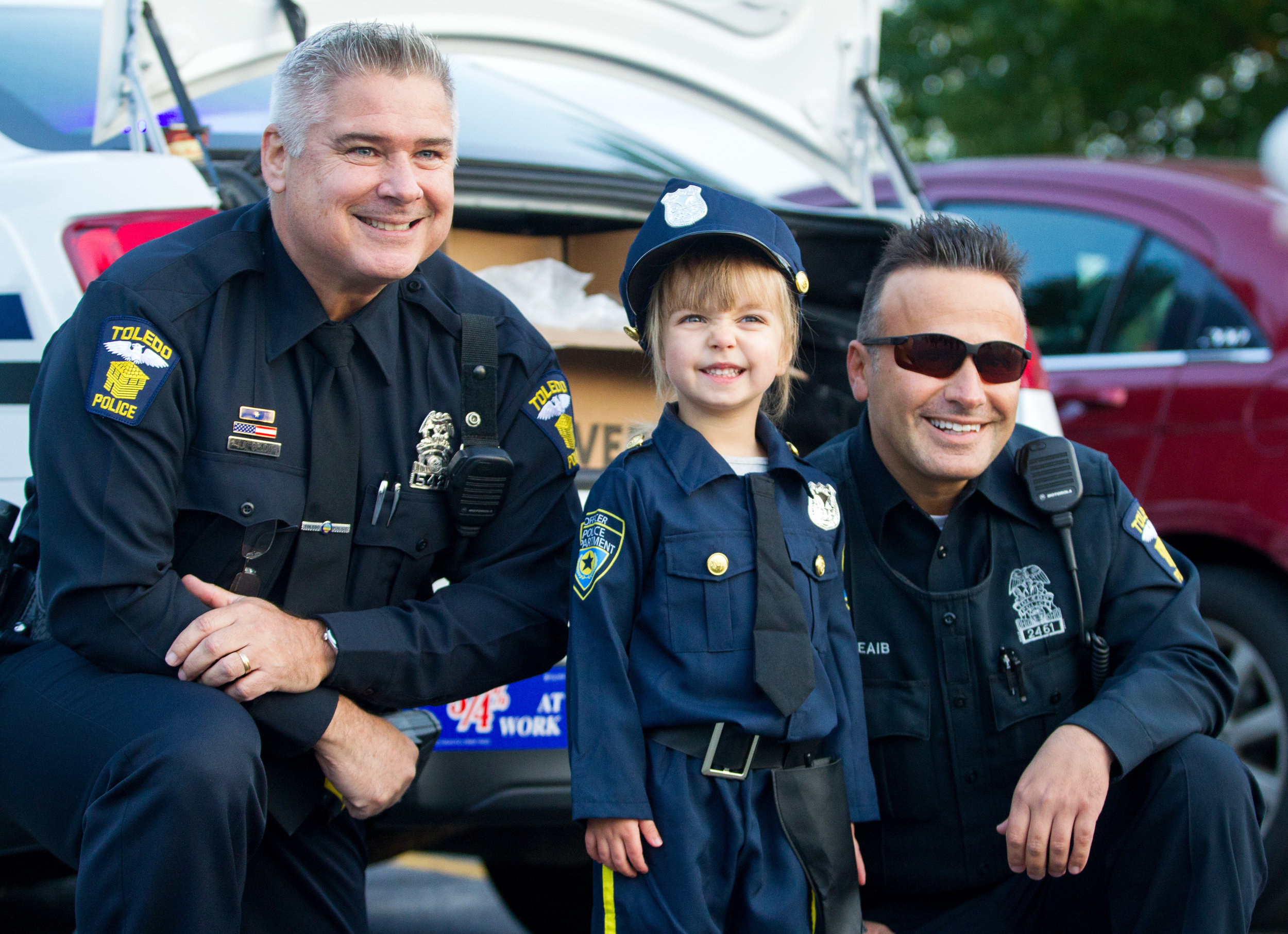 Toledo police officers Jim Below, left, and Hassane Cheaib, right, pose with Morgan Mahaney, 3, during the Winterfield Venture Charter Academy's Fall Festival at the school on Wenz Rd. in Toledo on Tuesday, Oct. 25, 2016.