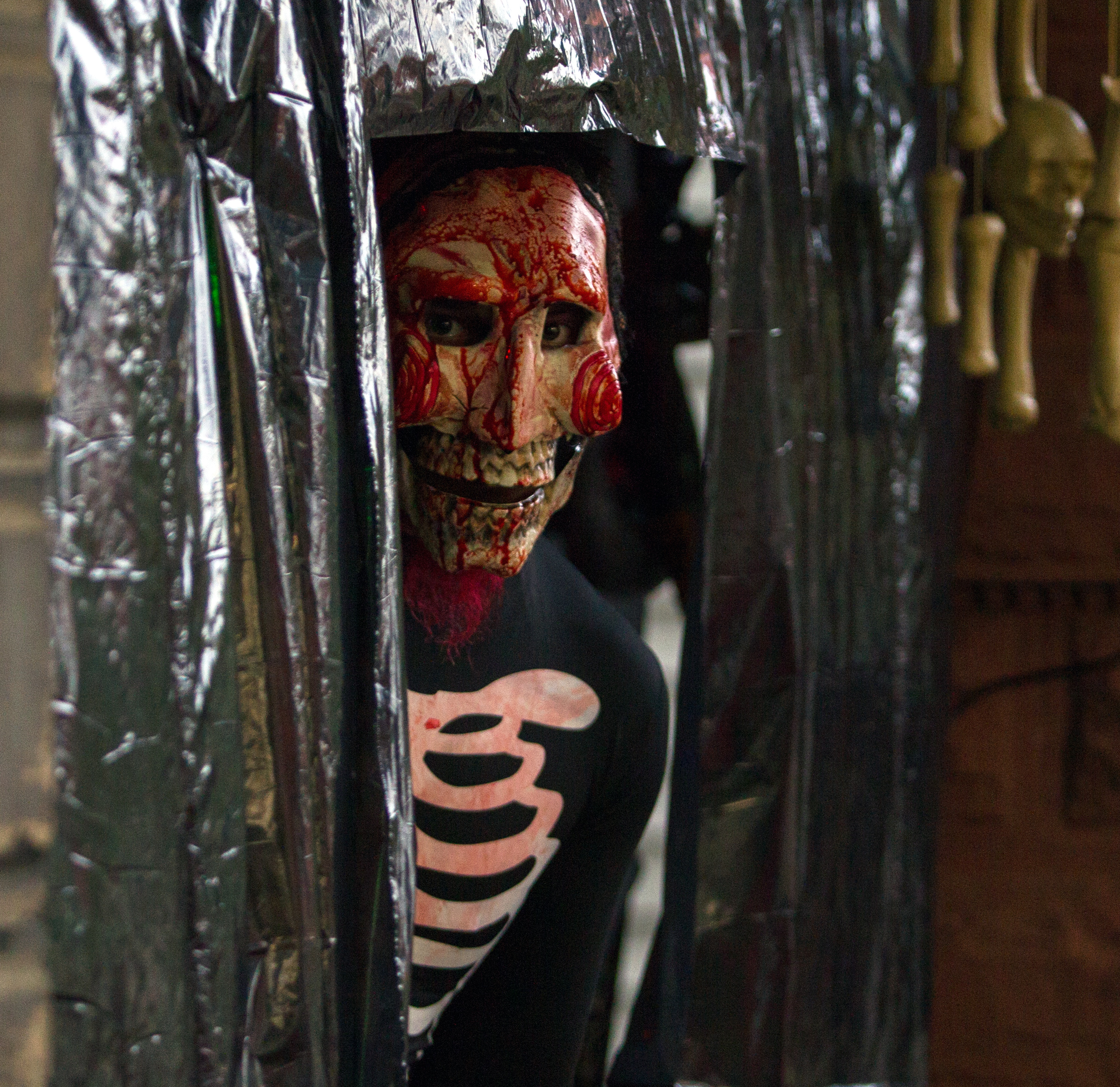 Jake Reynolds peeks out from a plastic curtain as he participates in a haunted house on University Blvd. in Toledo during trick-or-treating on Halloween on Monday, Oct. 31, 2016.