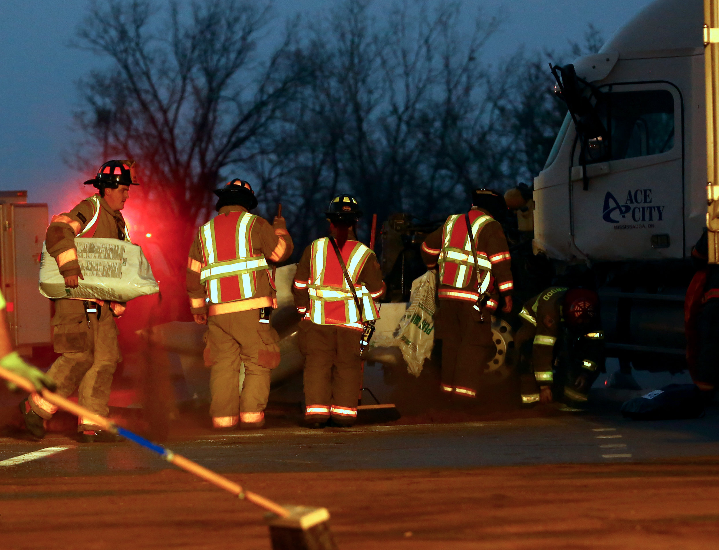 Members of Rossford Fire and Rescue work on spreading absorbents on the diesel leaking from a jack-knifed semi on I-75 Northbound in Northwood near the Wales Rd. entrance ramp on Tuesday, Nov. 8, 2016.
