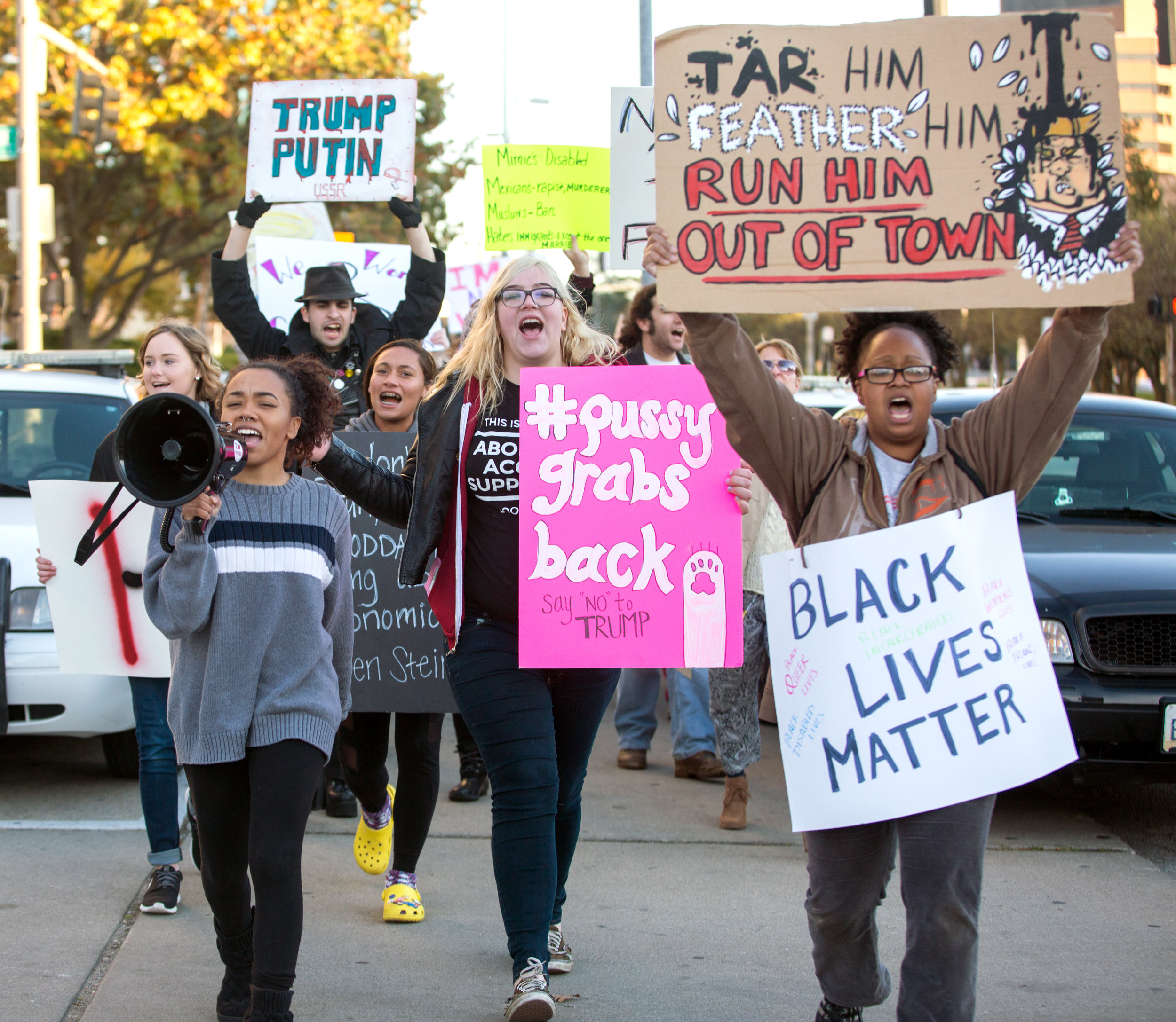 Angel Esparza of Toledo, left, leads the protest march that she organized down Jackson St. past the Toledo Police Department with Allie Lahey, center, and Shannon Frye, right, in downtown Toledo on Saturday, Nov. 12, 2016.