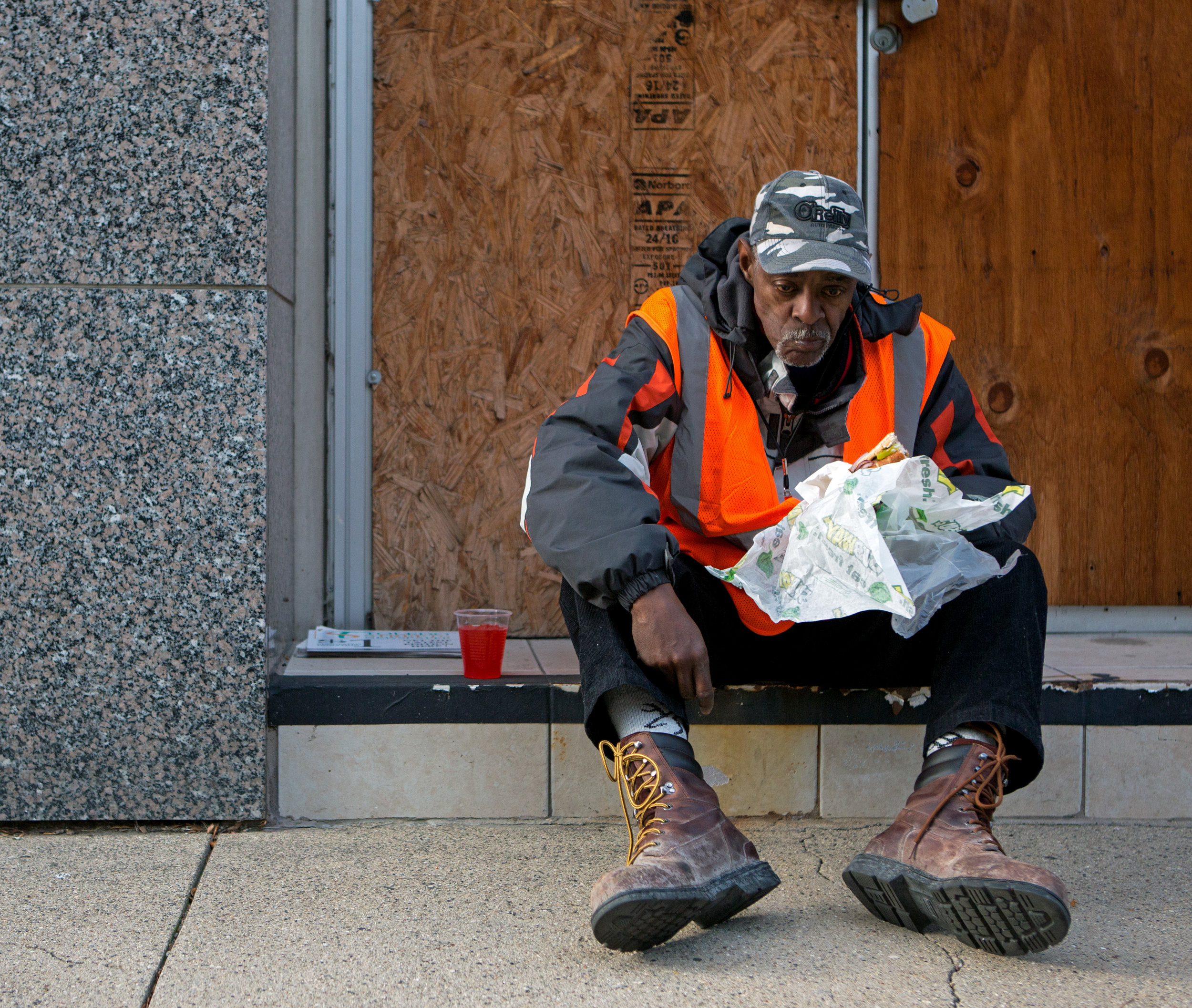 Ron Gage eats a sandwich on a step of a building on Superior St. while selling Toledo Streets Newspapers in downtown Toledo on Monday, Nov. 14, 2016. Gage sells the papers so that he can earn enough throughout the day for a bus token to his other job in West Toledo.