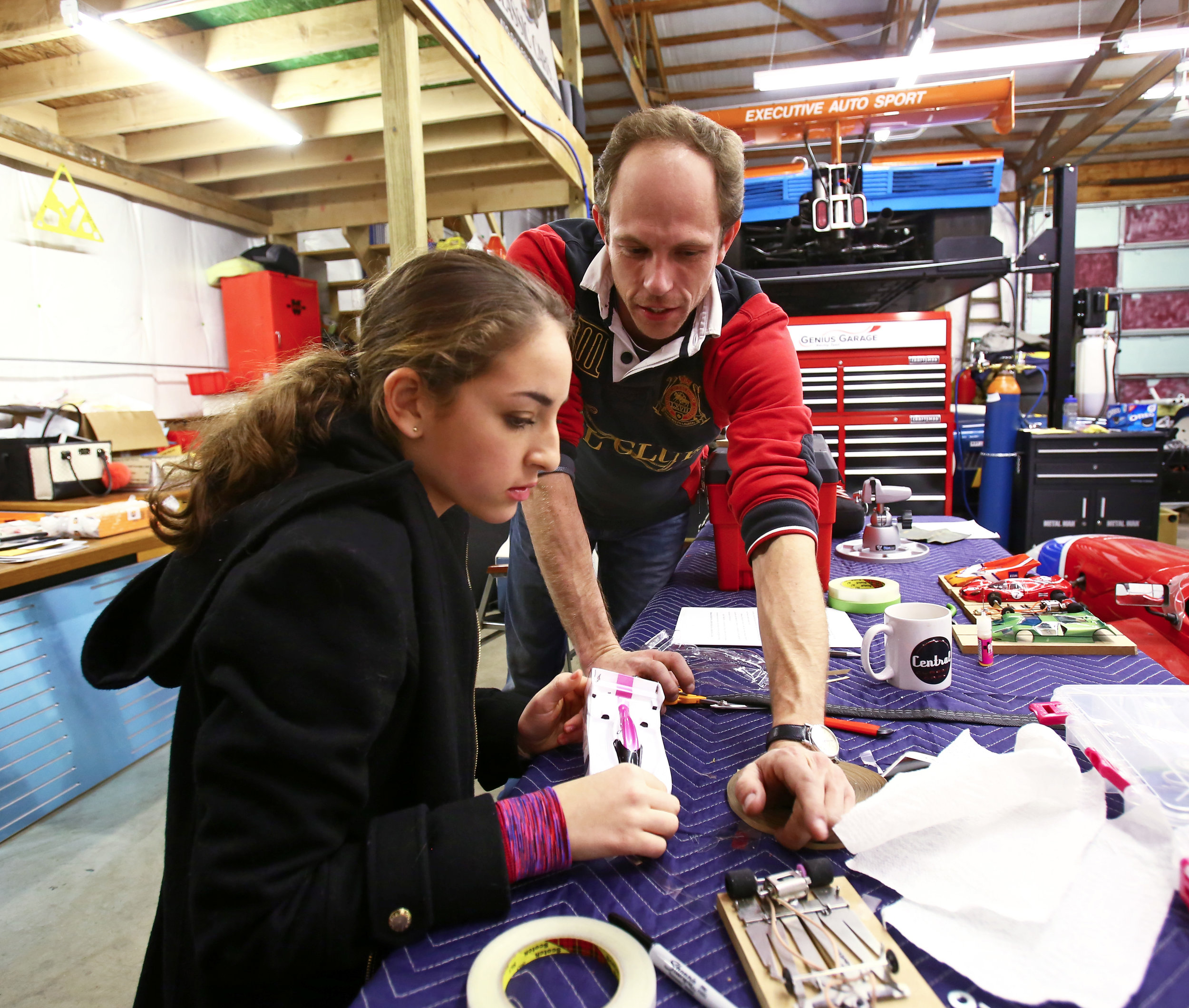 President of Genius Garage Casey Putsch, right, gives Kenna Edwards of Sylvania pointers on how give her slot car some extra stability on the track at the Genius Garage Racing Team's garage located in the Sylvania Business Plaza on W. Central Avenue in Sylvania, Oh. on Monday, Dec. 12, 2016.