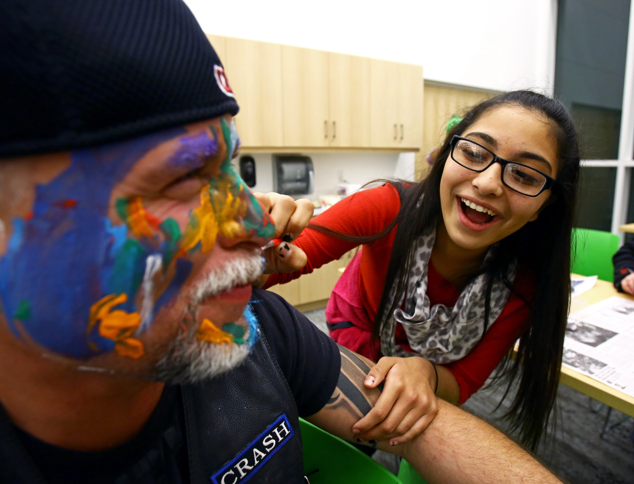 """""""Little Shorty"""" of Toledo paints on Warriors for the Children member """"Crash's"""" face during the arts and crafts portion of the monthly Bullfrogs Against Bullying peer support group at the King Road Branch Library in Sylvania, Oh. on Monday, Dec. 19, 2016."""