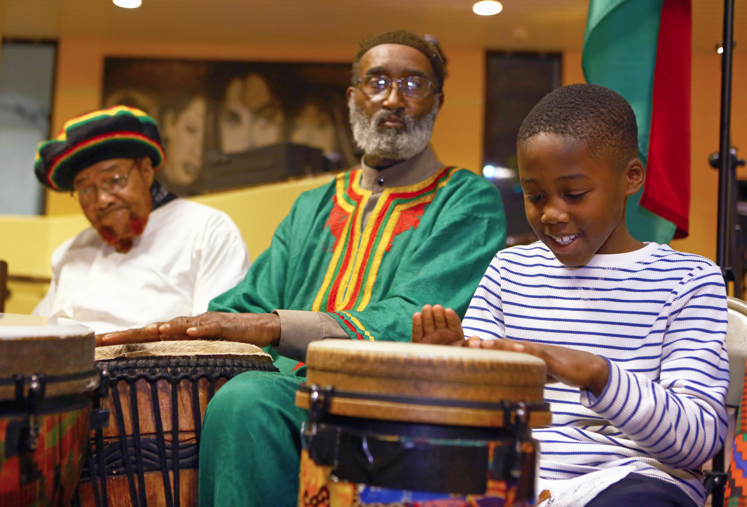 Tariq Harris, 9, of Toledo, right, plays a djembe with Kewape, center, and Imam El Allizar, left, during the first night of Kwanzaa celebrating umjoa, or unity, at the Fredrick Douglass Community Center in downtown Toledo, Oh. on Monday, Dec. 26, 2016.