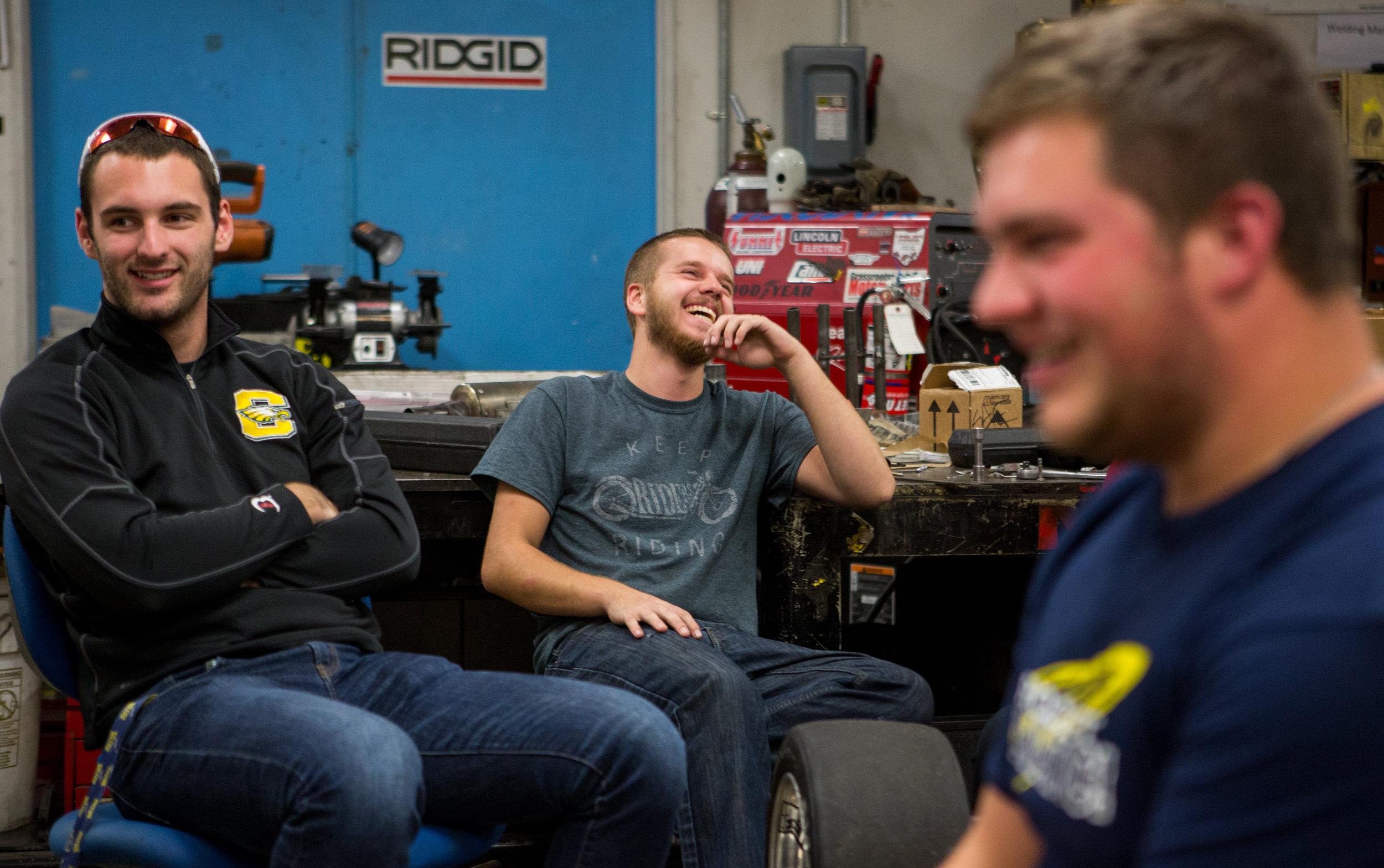 Jared Schaufele, left, and Colton Niese laugh with the rest of the team during one of their weekly planning meetings in the Formula SAE team lab.