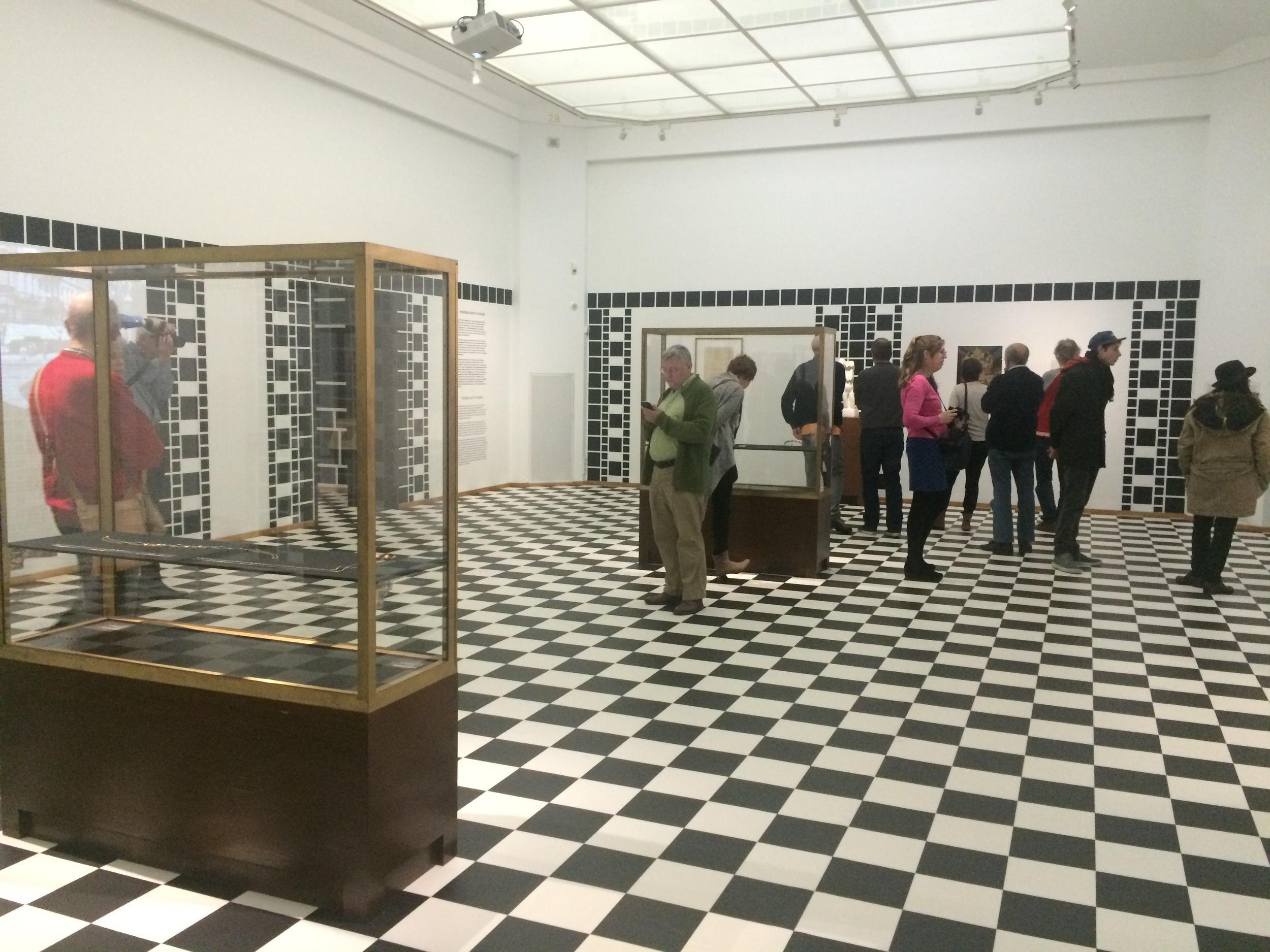 De eerste zaal van de tentoonstelling. De gouden vitrines steken mooi af bij het zwart/wit op de vloer en muren.