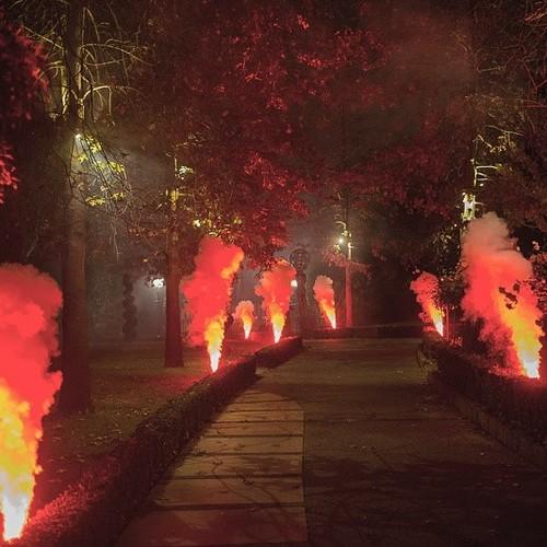 Geyser smoke jets lined either side of walkway shooting column of red smoke - Blaso Pyrotechnics