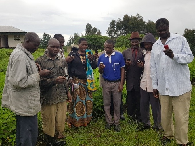 Farmers in Tanzania using mobile phones to receive information about improving agricultural productivity. Taken in January 2018 during Tanzania field mission by Landell Mills' Evaluation team