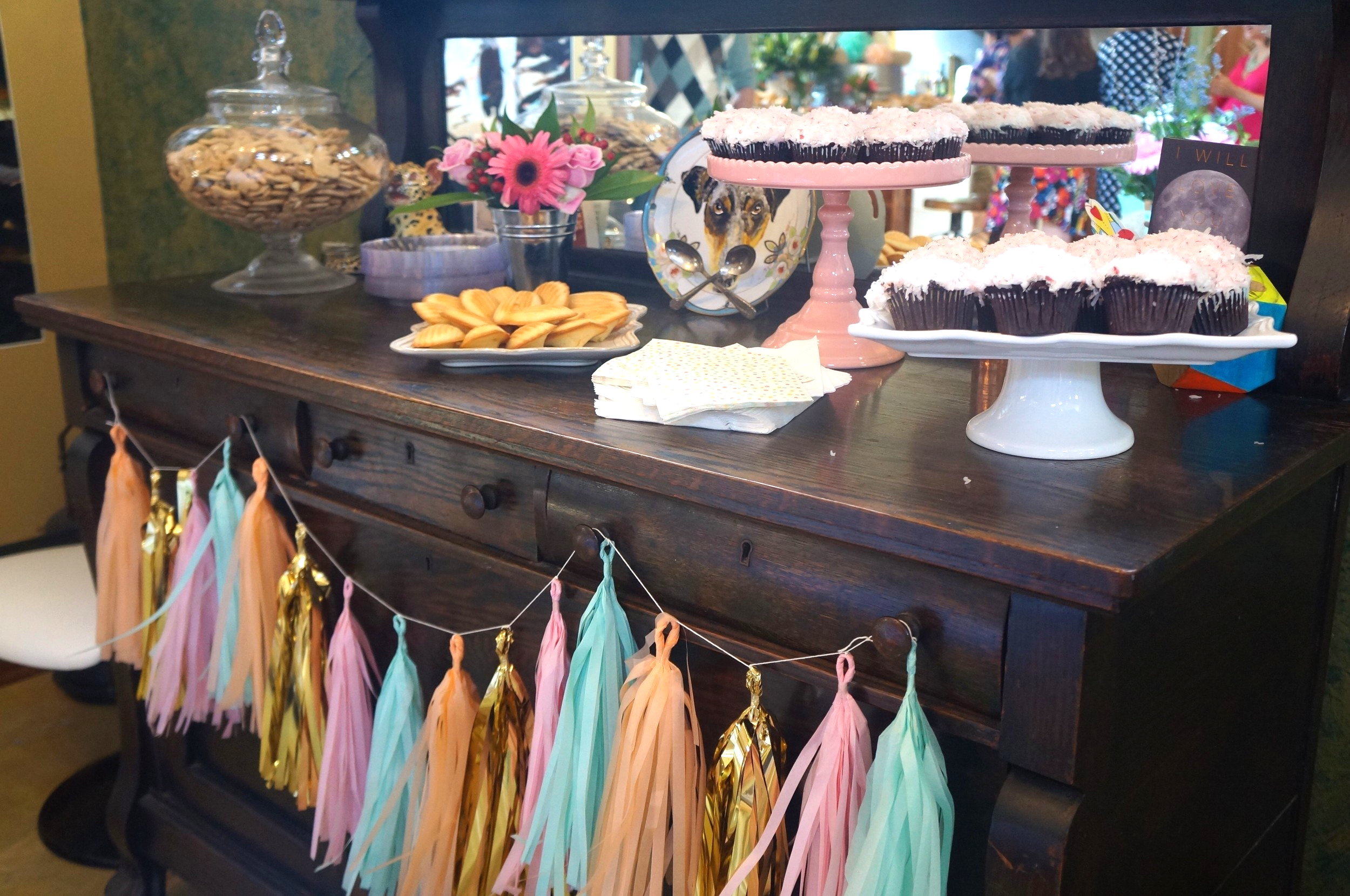 Dessert table with pink coconut cupcakes and madeleines