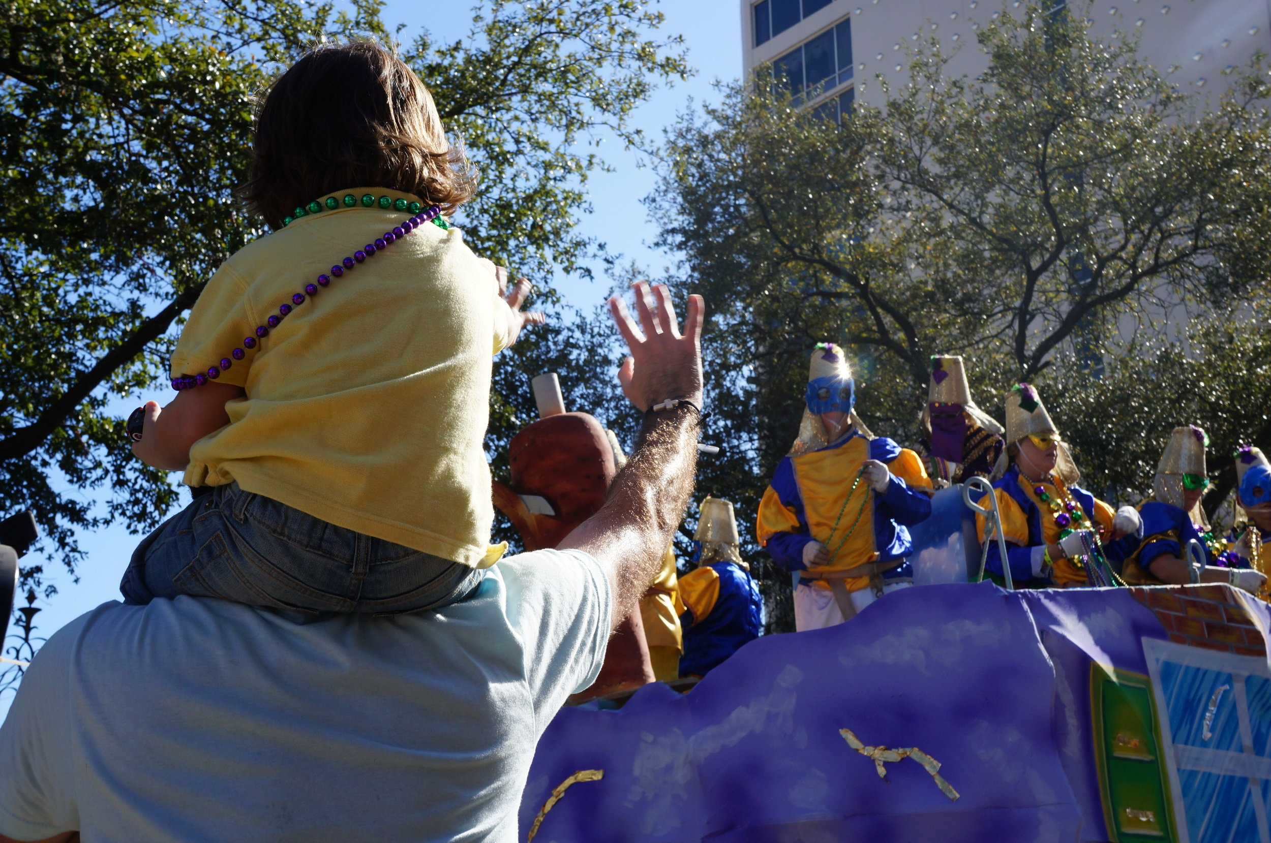 catching beads from parade float in new orleans