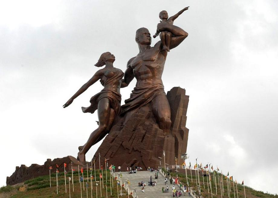 The African Resistance Monument, Dakar, Senegal.   Of incredible scale (49 meters tall (160 feet)! - by way of reference, the Statue of Liberty is 151 feet from base of pedestal to the torch), an observation deck in the man's forehead! and bold artistic lines! – look at the protagonist's chiseled quads erupting out of the chiseled rock!, his abs and biceps lifting his child and his beautiful wind-swept lady!, the angles pointing to the future!