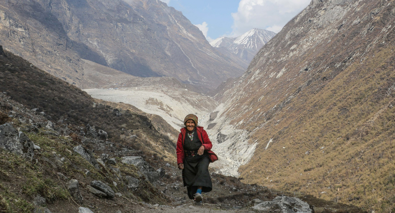 A nepali women with the site of the landslide scaring the valley behind her. Trees can be seen lying on the opposite side of the valley, blown over by the force generated by the slide.  PC @isamcc