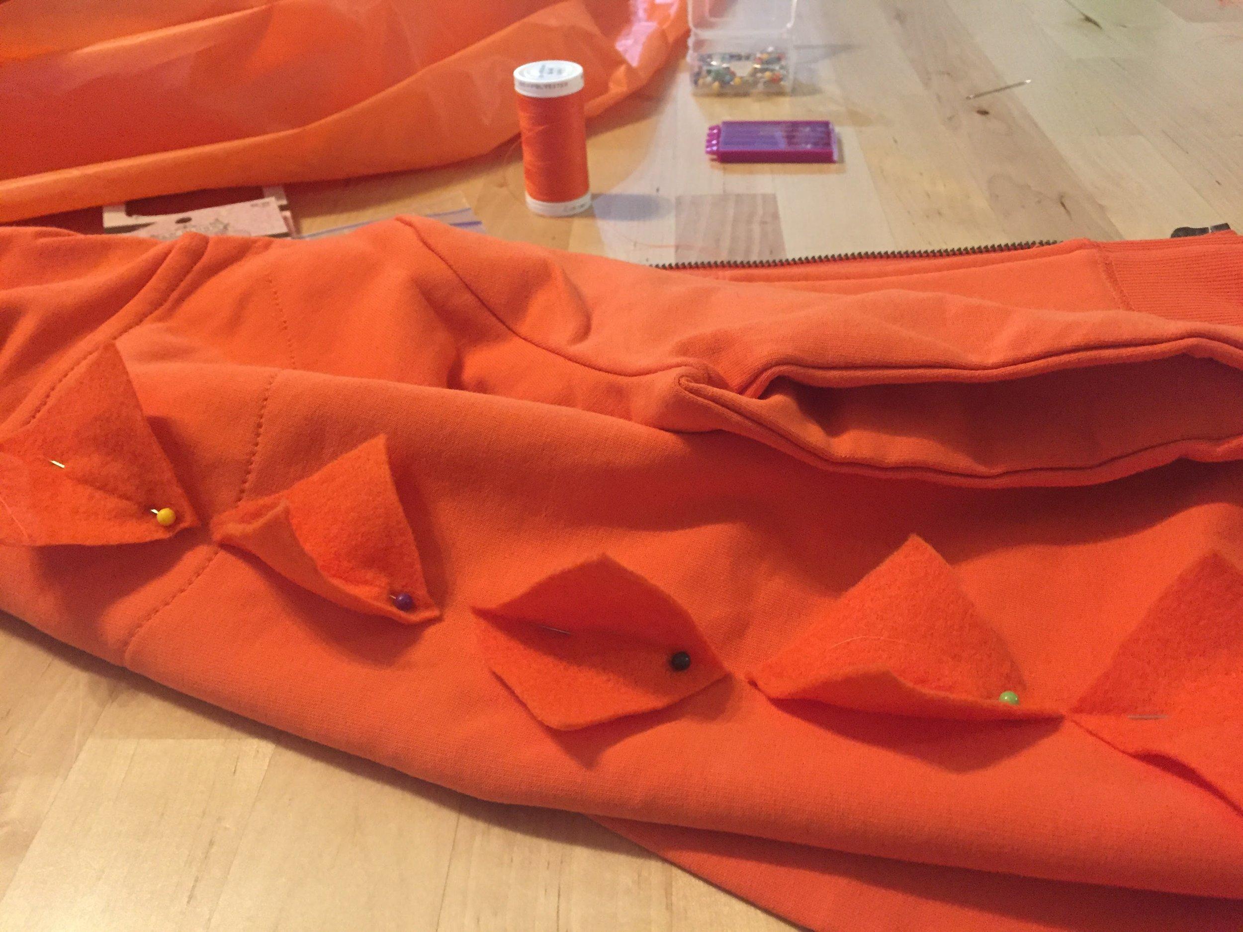 Pin the spikes to the hoodie before sewing #halloweendinodiy