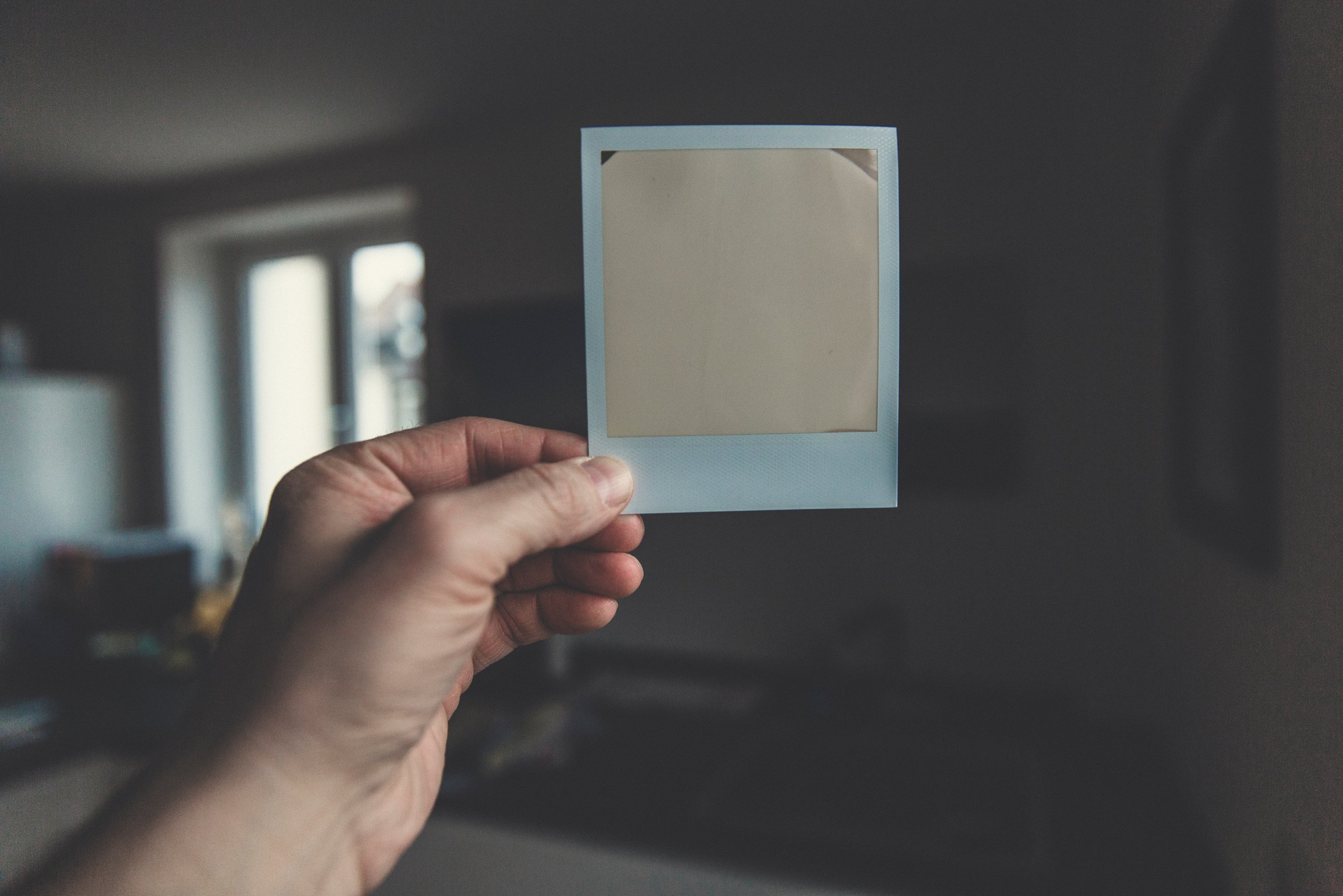 Color photograph of hand holding an undeveloped Polaroid