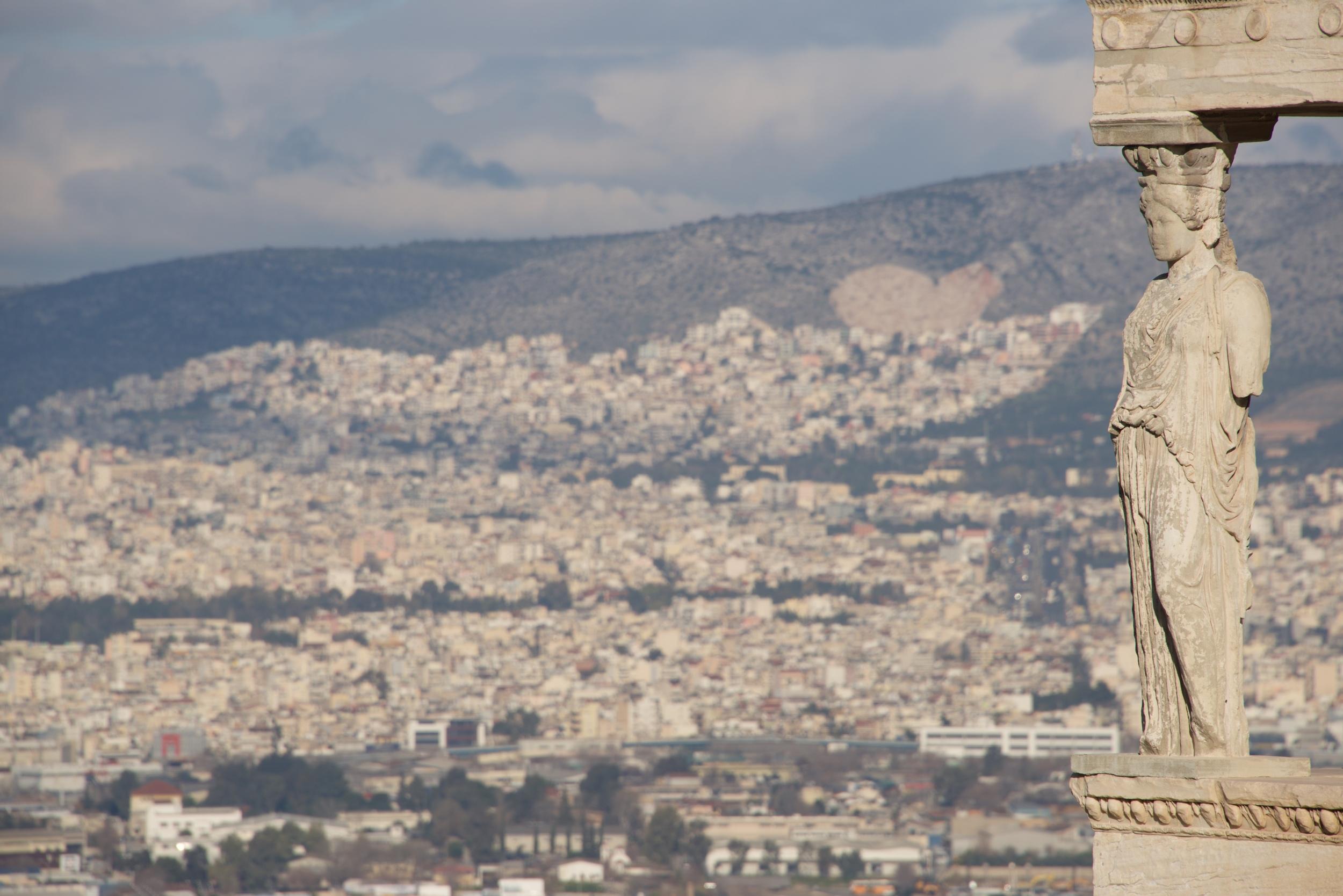 Hills of Athens seen behind Erechtheion caryatid.jpg