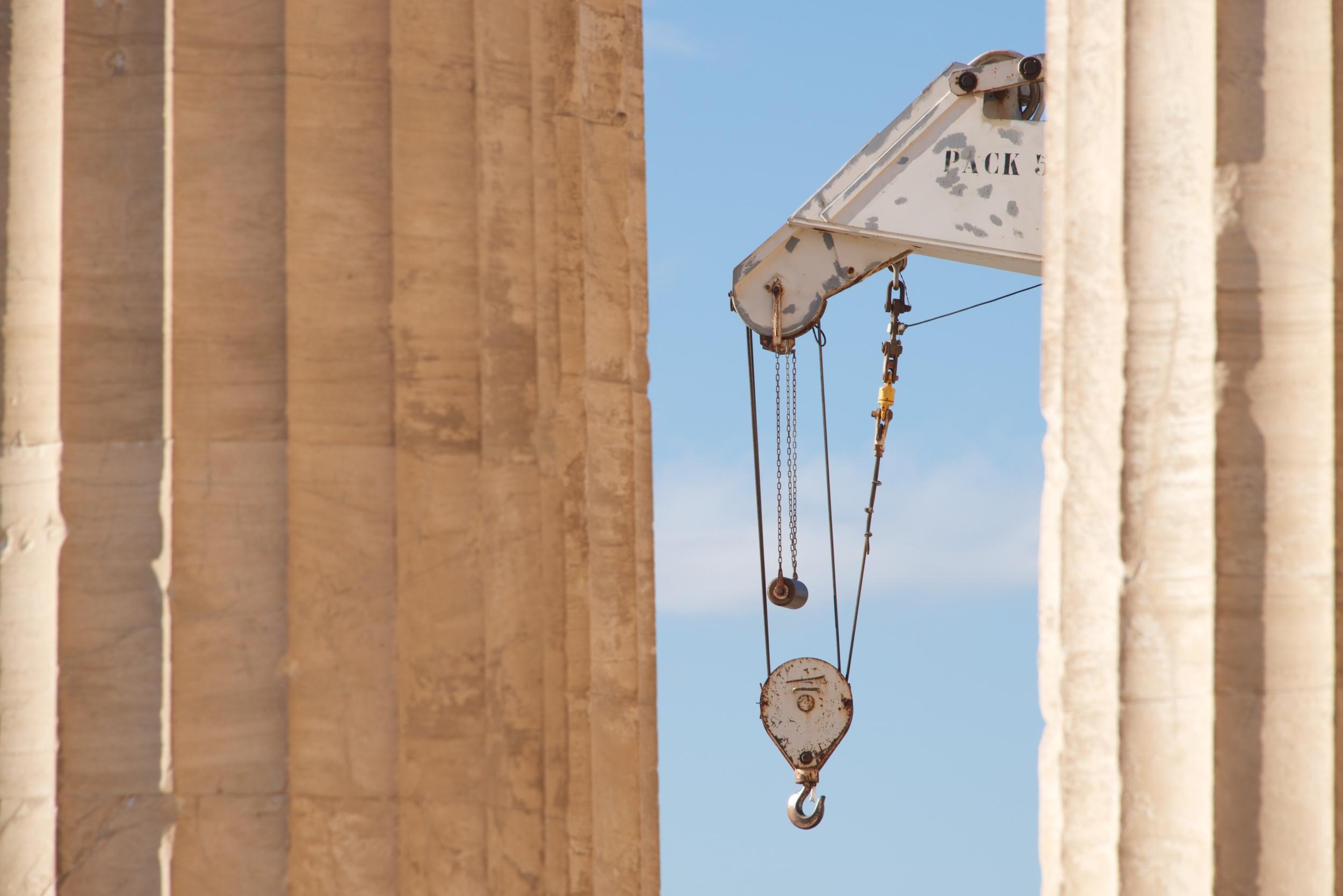 White crane between two marble Parthenon columns.jpg