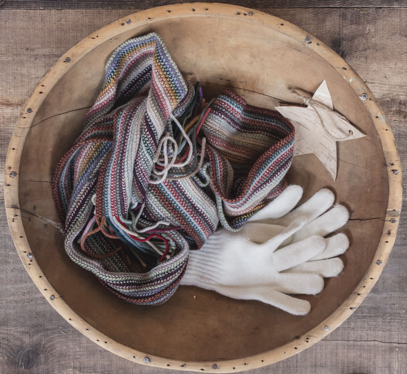 bowl of mittens and scarves as holiday decoration