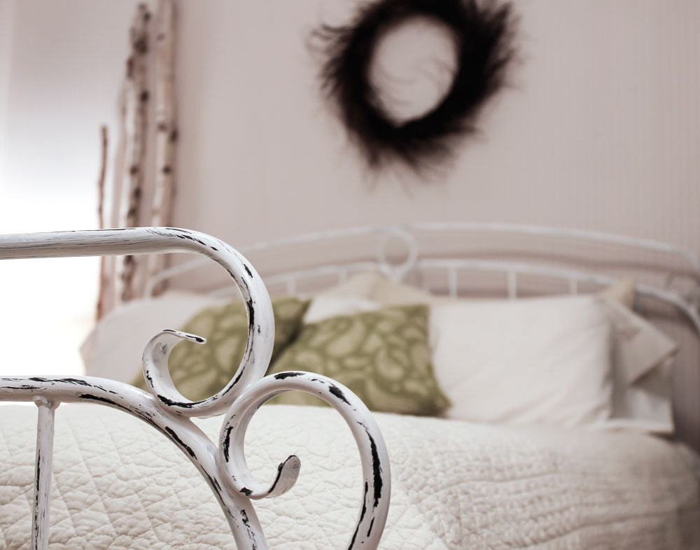 painted iron bed in rustic bedroom