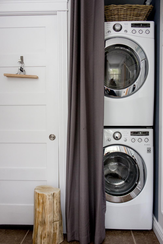 使用窗帘和拉杆将可堆叠的洗衣机和烘干机隐藏在浴室中