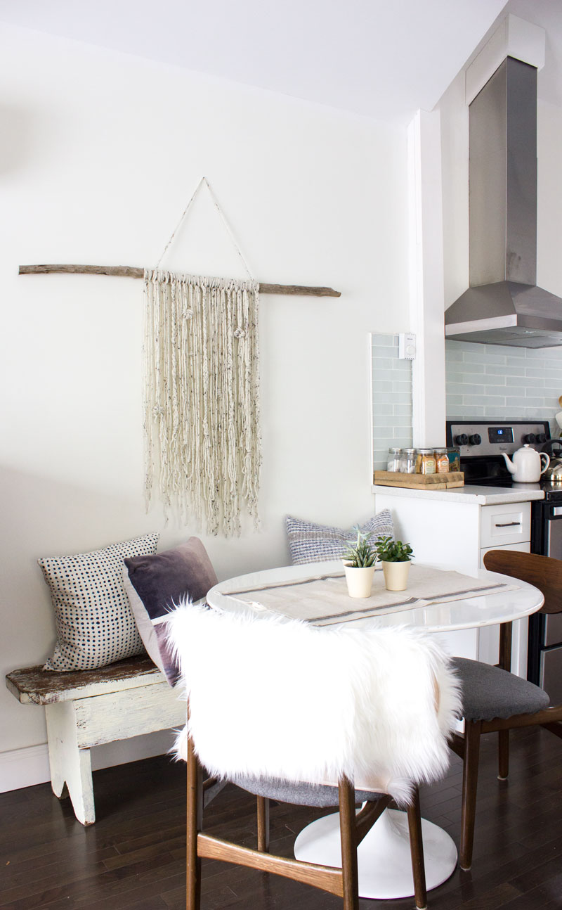 winter dining nook with stick and yarn wall hanging
