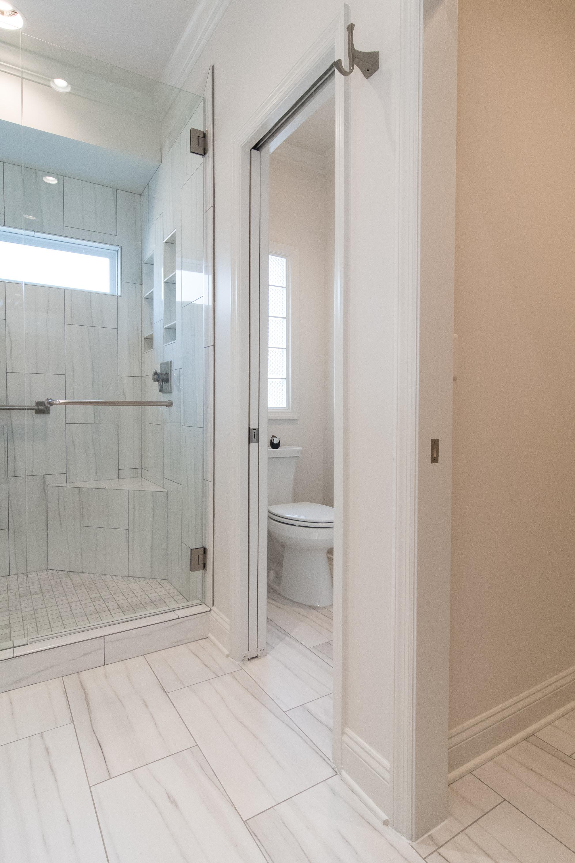Walk-in shower, window, water closet, barn door, toilet, whisper recessed light fan, niche, shower bench, frameless glass, large format tile, Vestavia Hills, Liberty Park, Alabama, Remodel, Renovation.