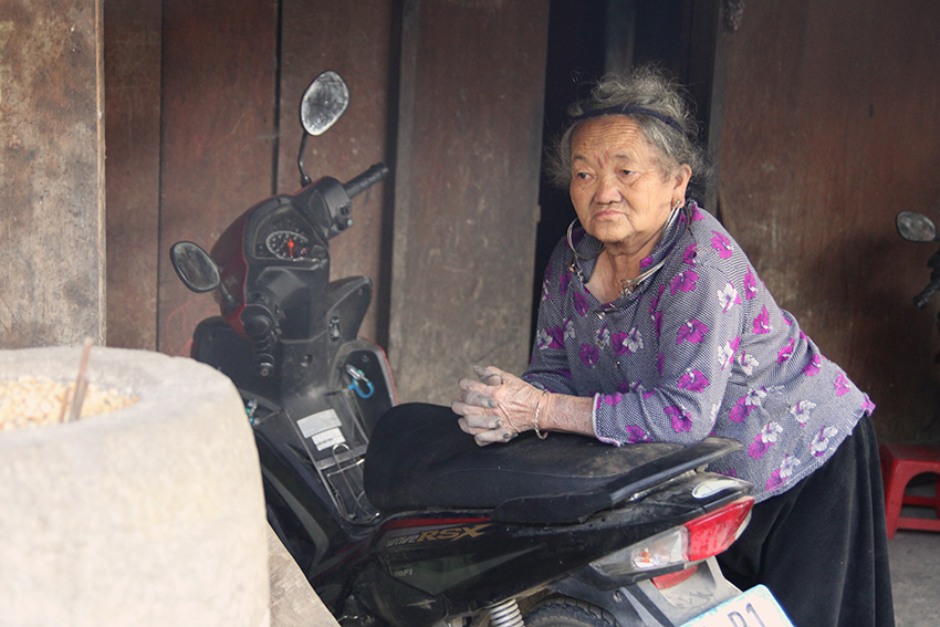 So's mother rests against a motorcycle, Sa Pa