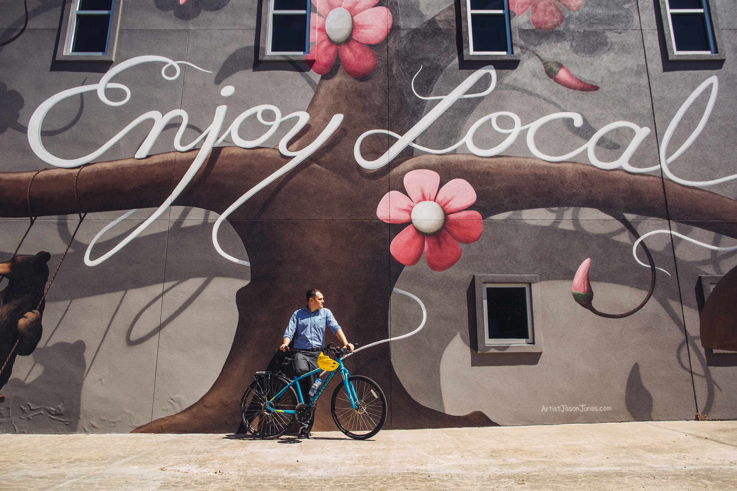 Dane Eifling reflects next to the newest mural at the Fayetteville Town Center.