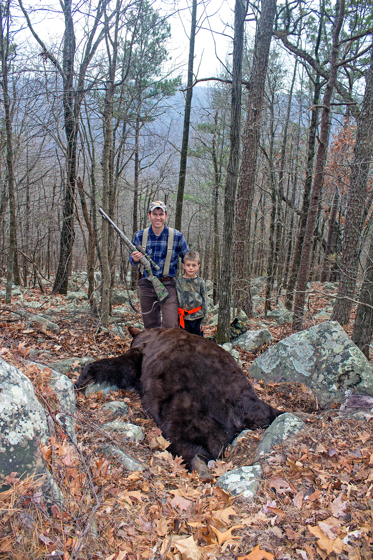 "Author Clay Newcomb and his son, Bear, stand over a bear harvested in Polk County. Estimated to weigh over 500 pounds, the ""color phase"" bear was officially scored at 19 11/16""."