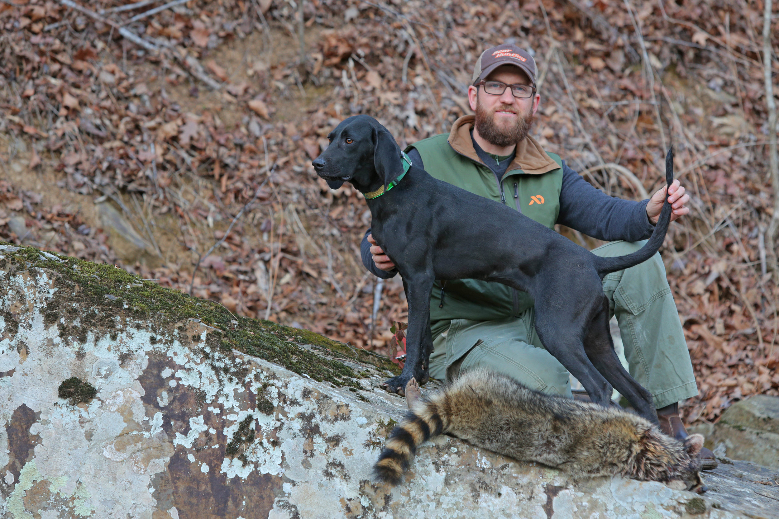 Author and avid hunter Clay Newcomb poses with his coonhound, Fern, and a freshly harvested Arkansas raccoon.