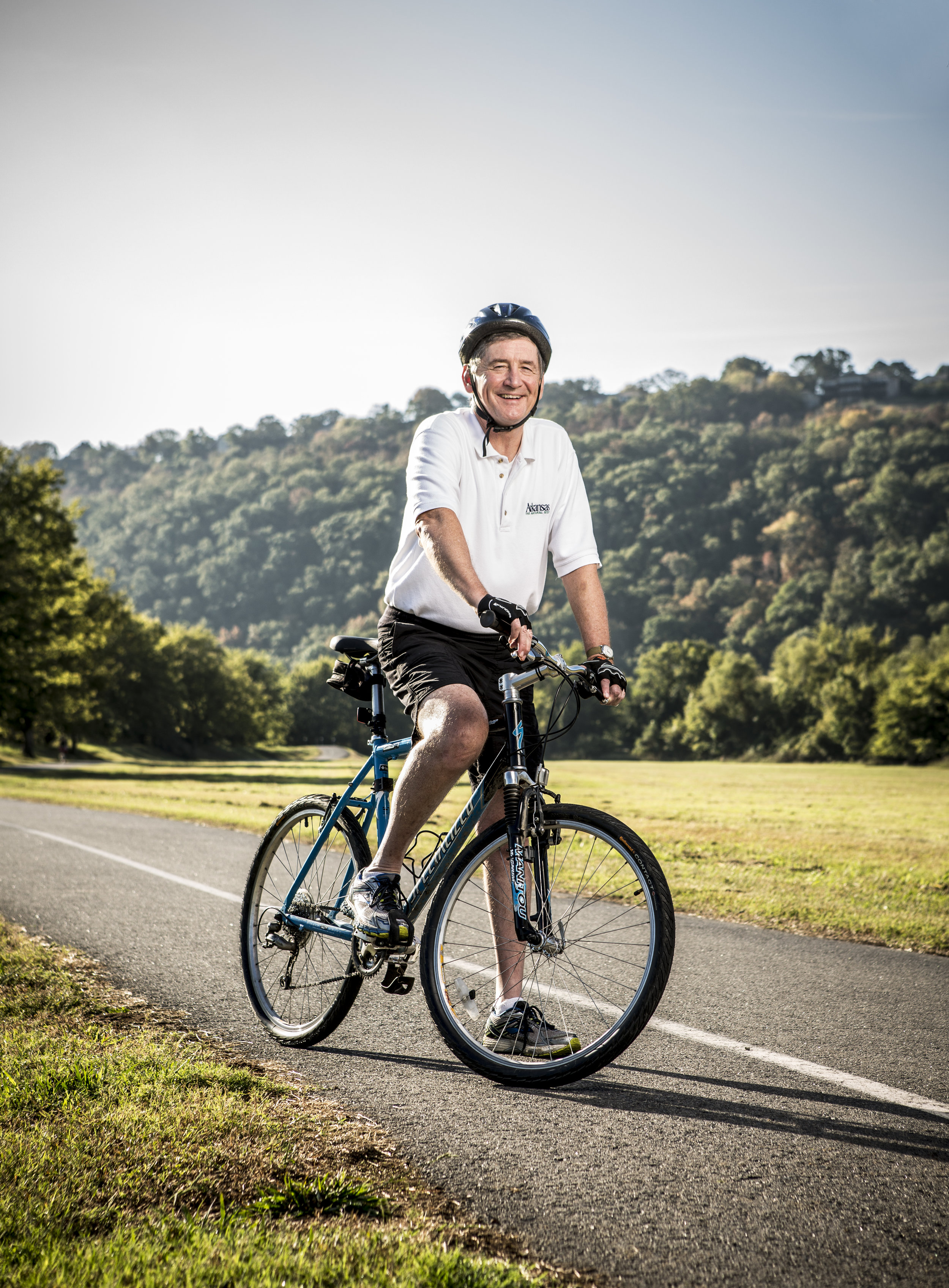 Arkansas Tourism Director Joe David Rice gets some fresh air on his bike at Two Rivers Park in Little Rock.