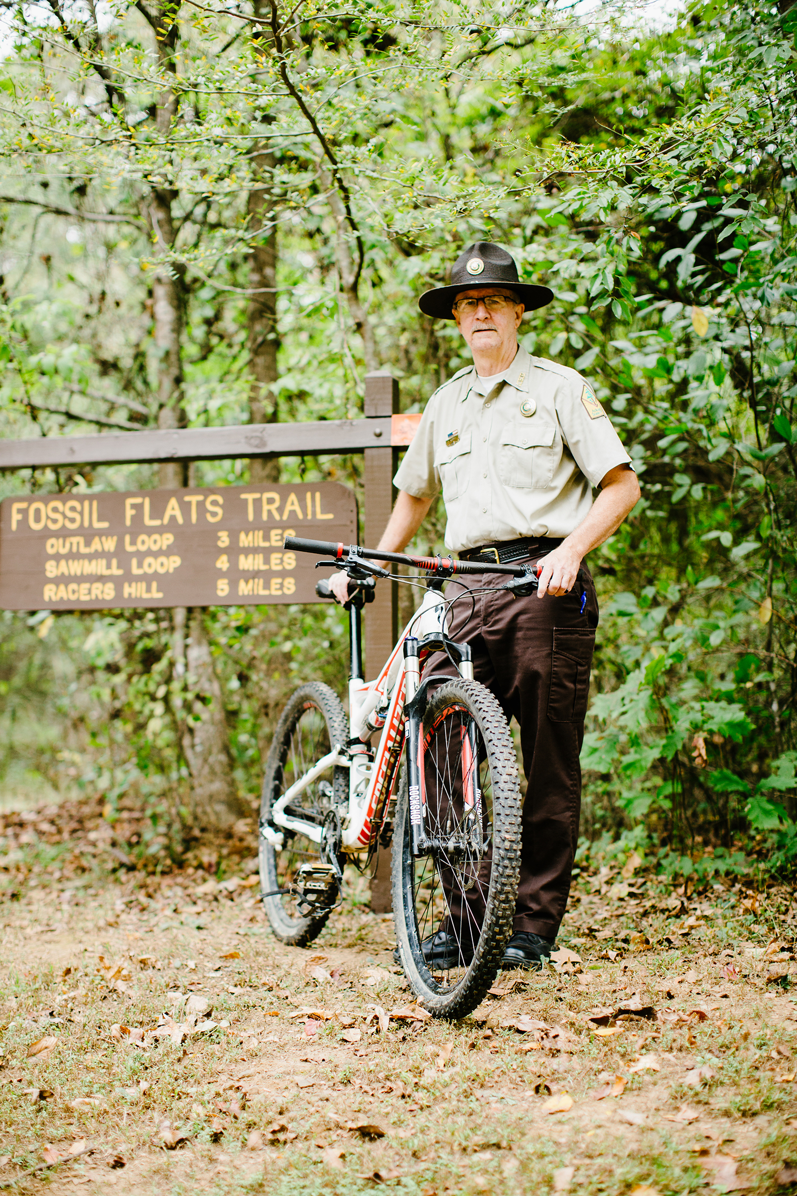 Devil's Den assistant superintendent Tim Scott stands at the trailhead of the Fossil Flats Trail, one of the first mountain biking trails in the state.