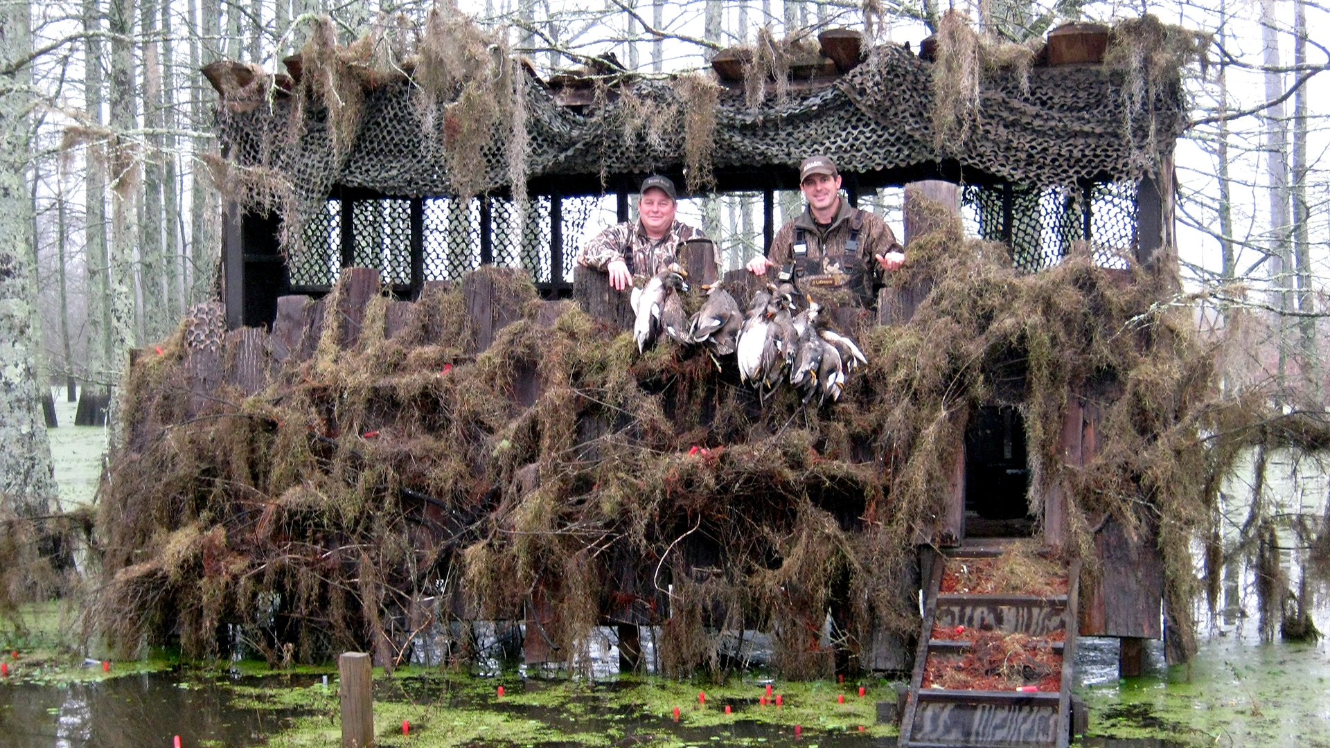 Tom Wingard and Paul Griffin show off their kill in one of several cypress slough blinds author John McClendon uses to entertain business guests.