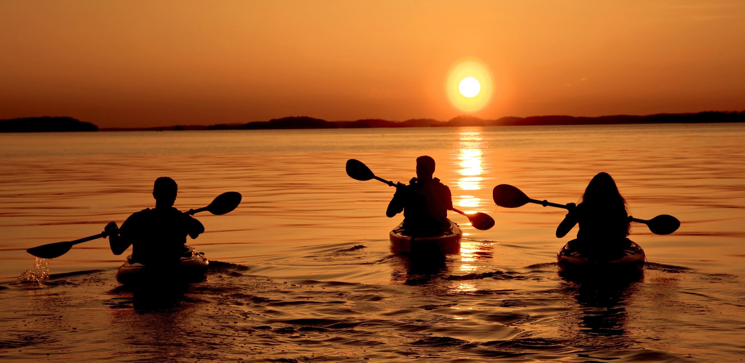 Kayakers take off into a Lake Ouachita sunset.