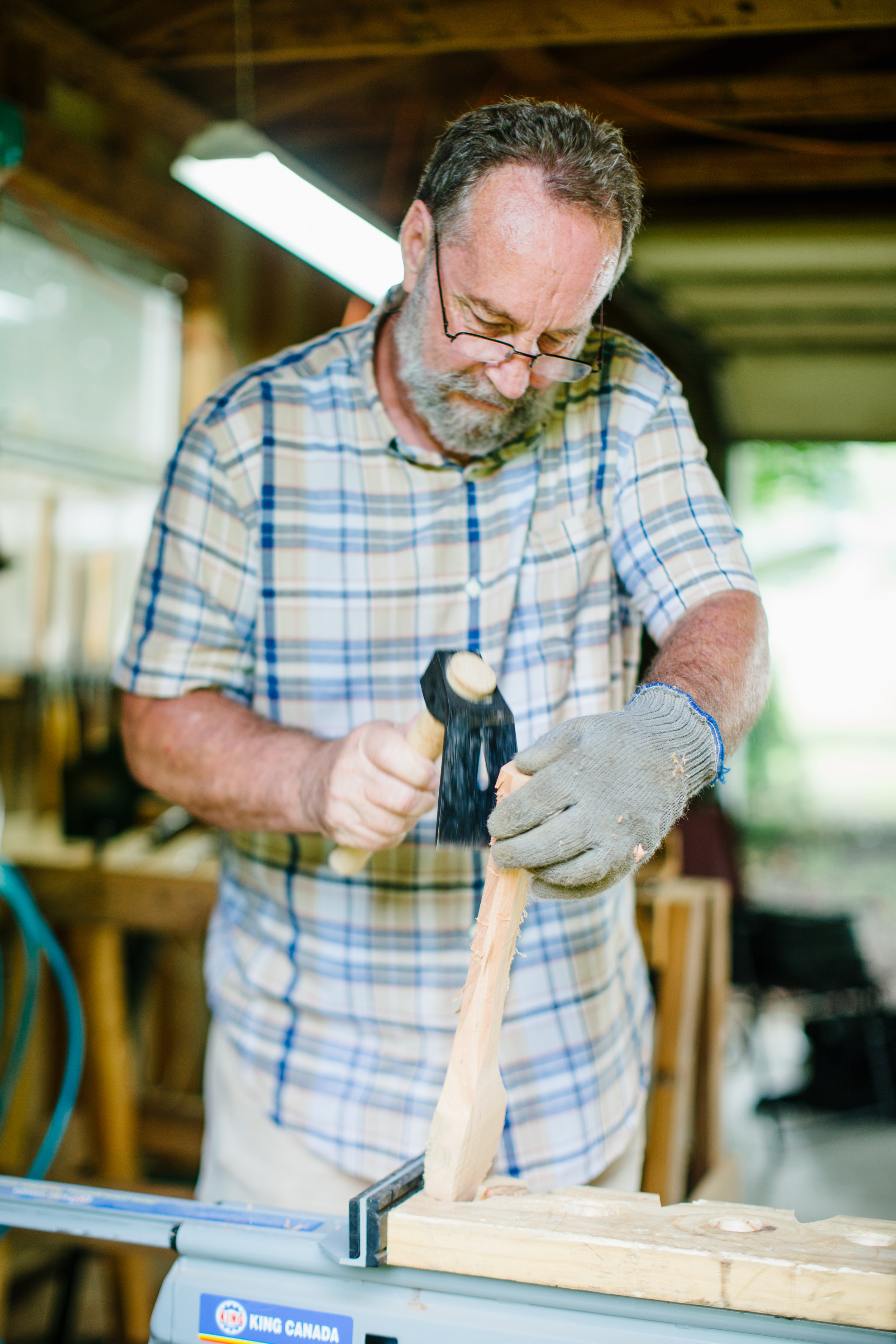 John Kirkpatrick uses an adze to begin roughing out the shape of the spoon.