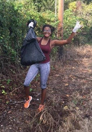 An excited volunteer pauses in collecting rubbish to throw the camera a peace sign.
