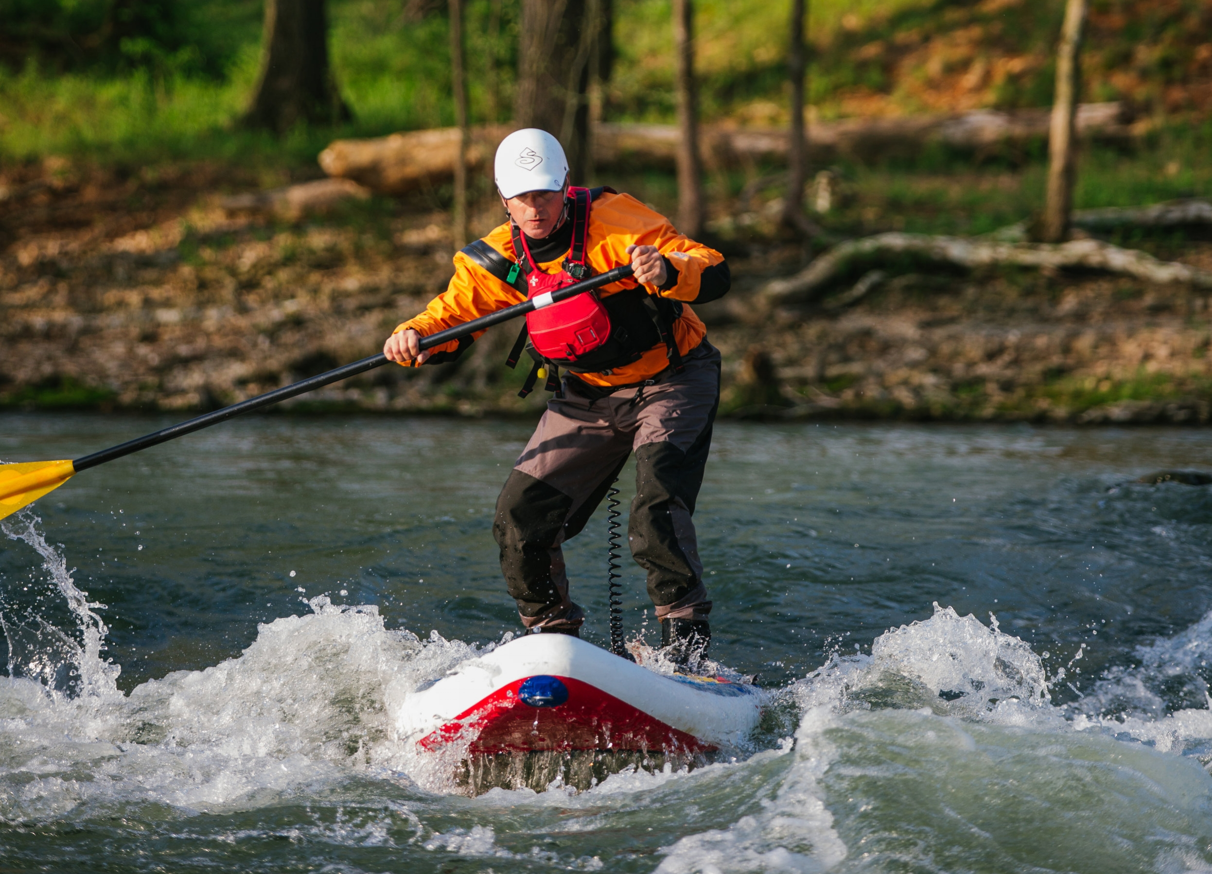 Rob Moody, one of two stand-up paddleboarding instructors in the state, navigates shoals at Siloam Springs Kayak Park.