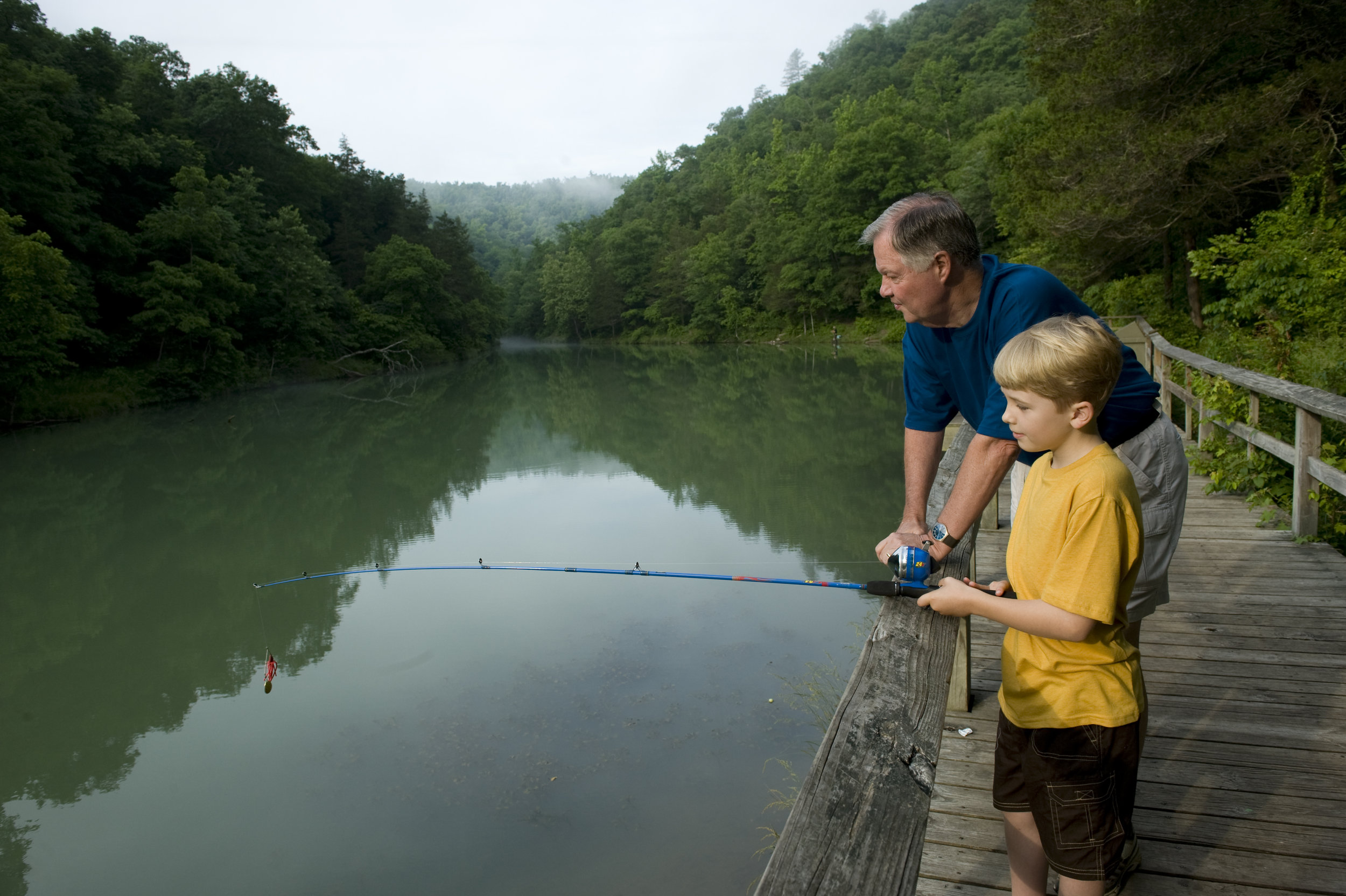 A grandfather teaches his grandson about the joys of fishing.