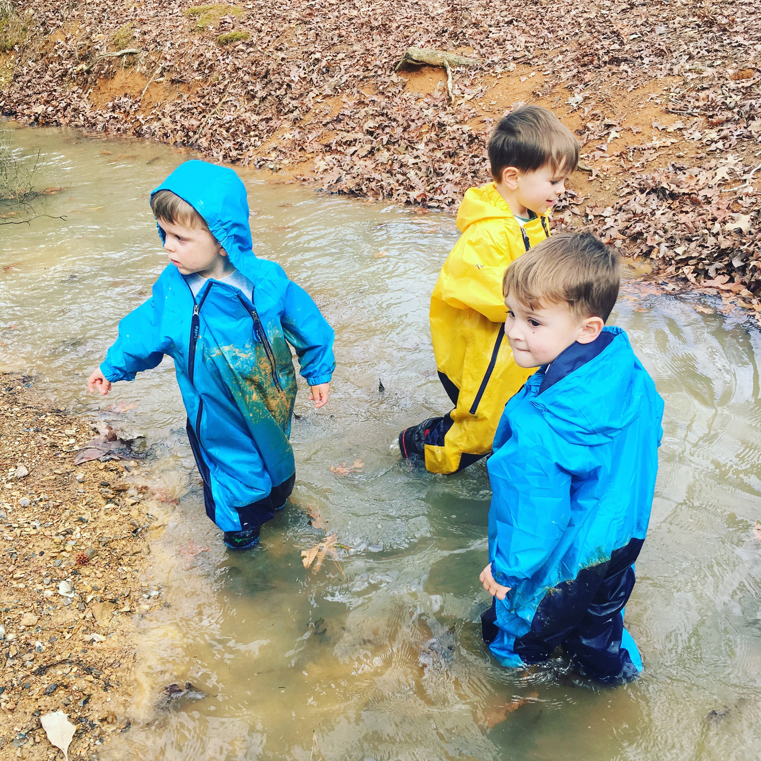 Children at the Lake Nixon Outdoor Preschool play in puddles and participate in the more usual preschool activity of finger-painting.