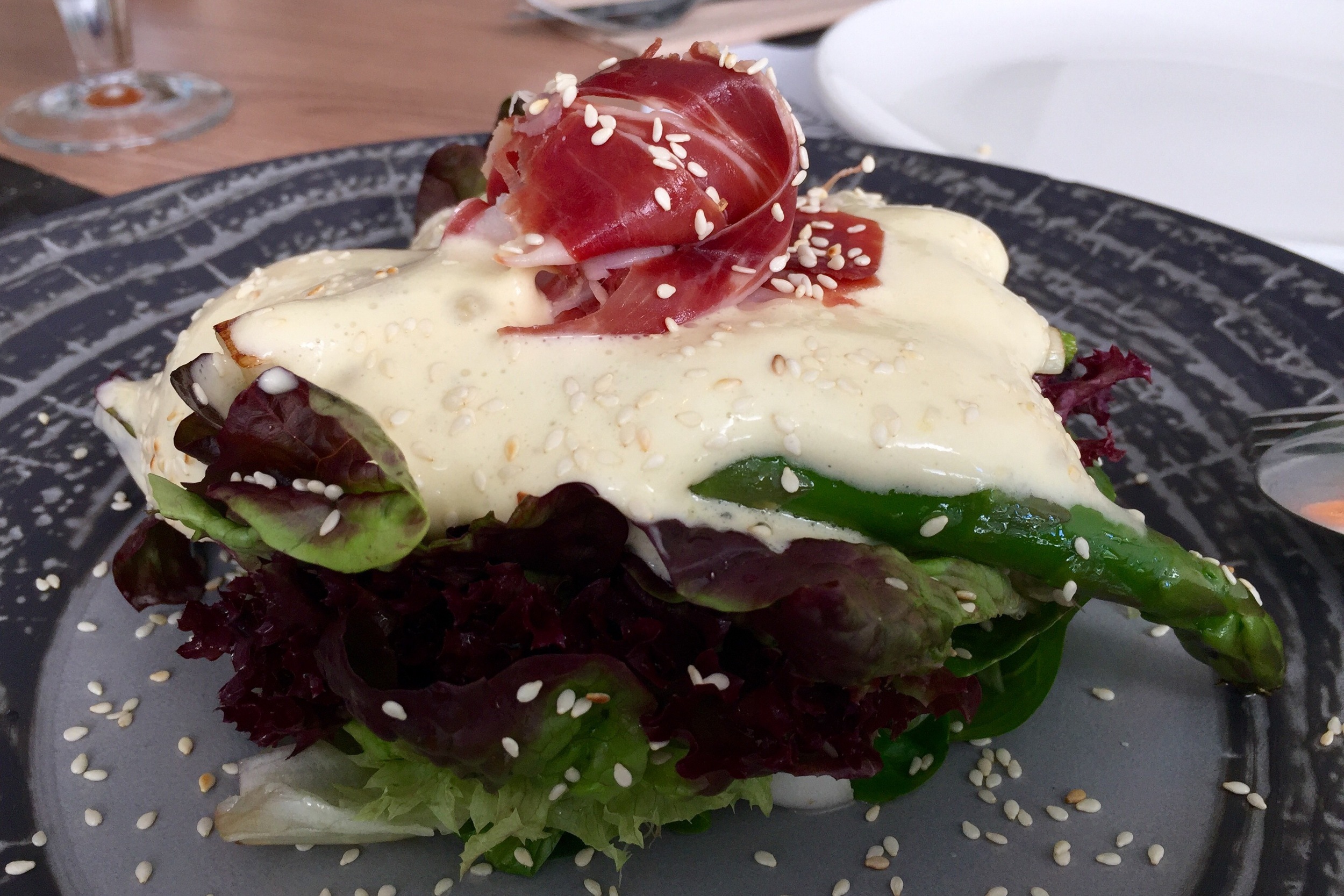 Warm asparagus salad with Iberian ham, mayonnaise foam, lime, and sesame vinaigrette
