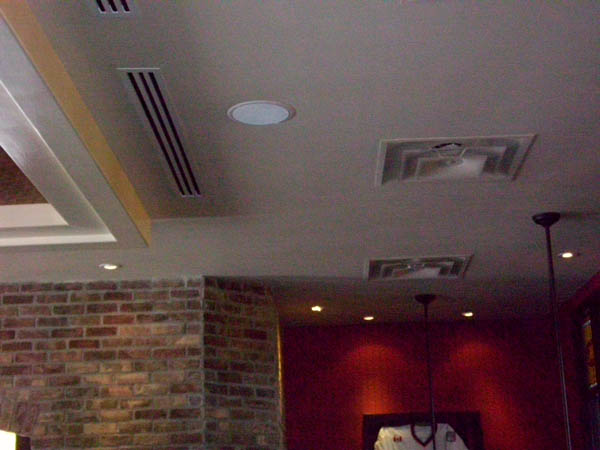 Ceiling speakers  often do the job well, if designed properly and are fitted for the décor.