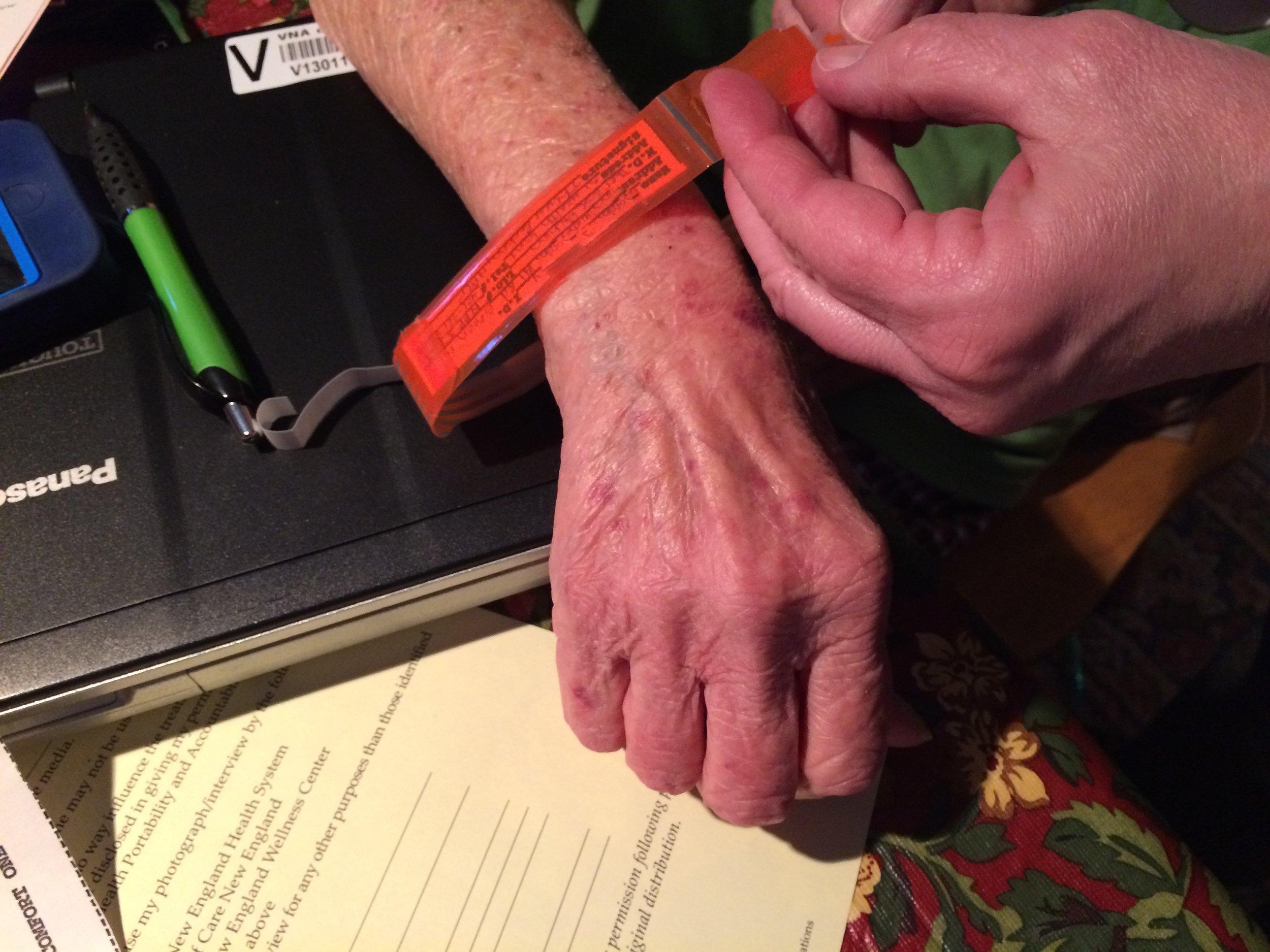 Visiting nurse Terry Rochon attaches a DNR bracelet to Debbie's wrist.