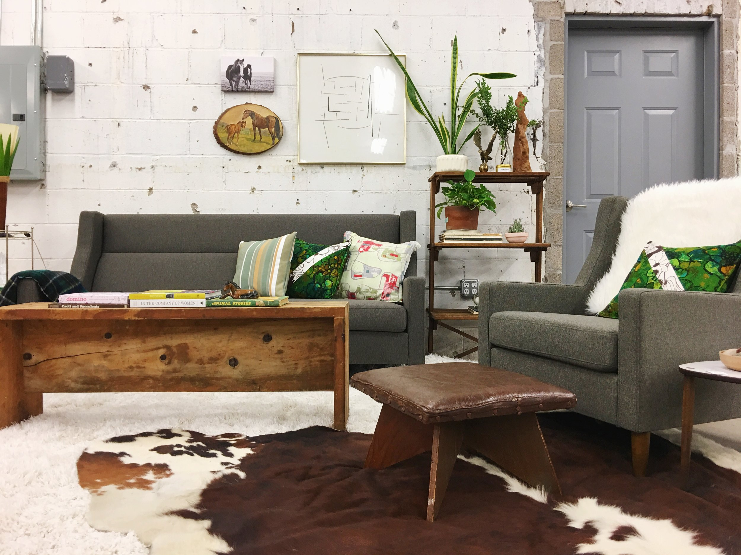 The unfinished wooden bench, worn leather stool, and horse art (Who doesn't love horse art?) are beautiful juxtapositions to the clean-lined, modern  Gus* Carmichael sofa and chair .