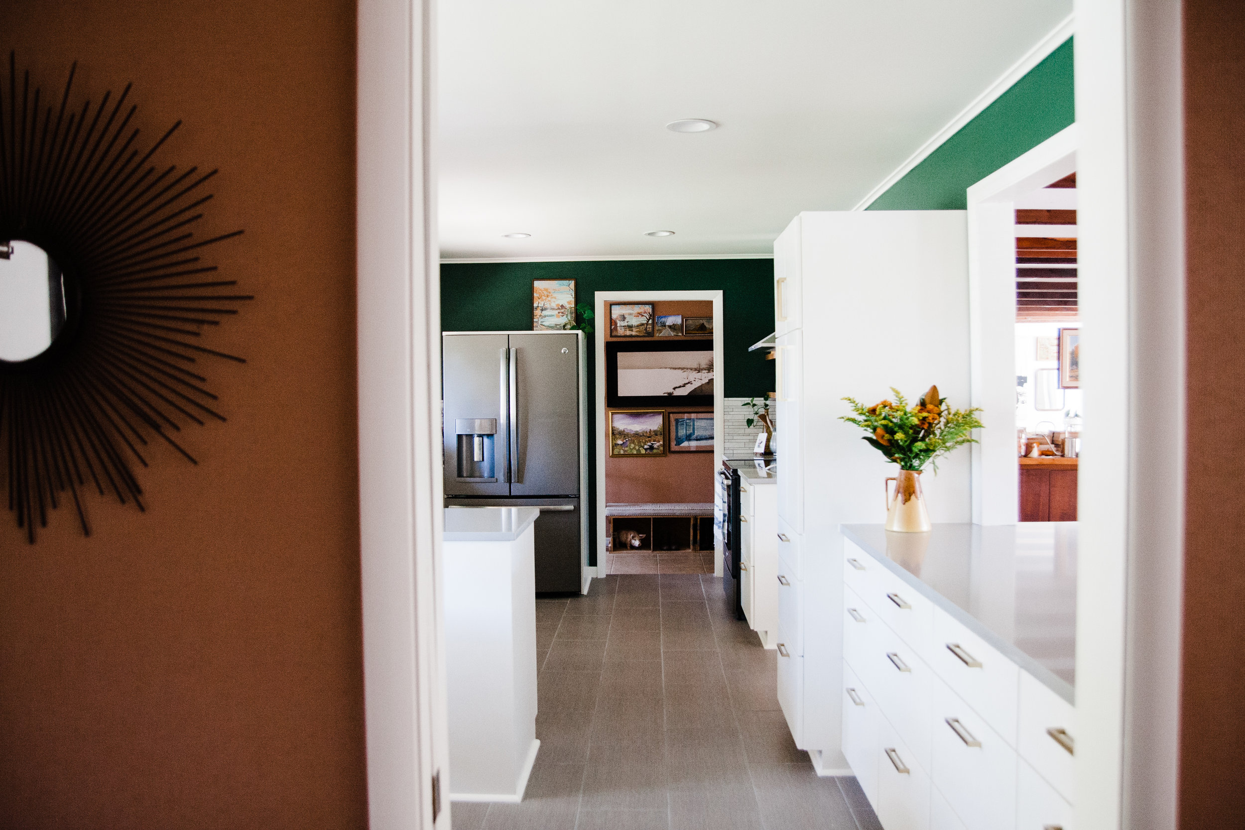 I love the view through the kitchen into the mudroom. The mudroom's landscape gallery wall feels like artwork for the kitchen too.