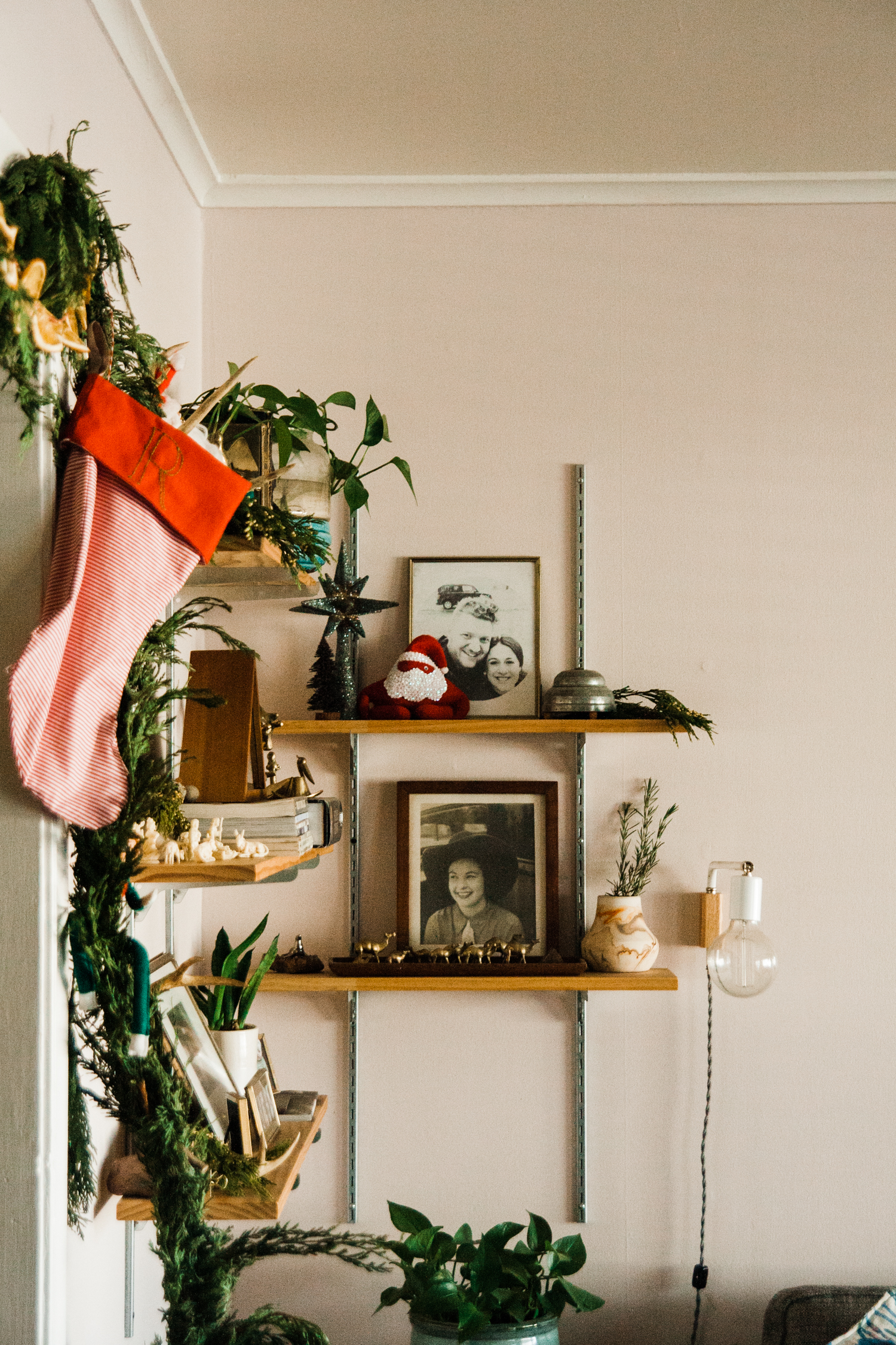 """At the time of these photos, I just started embroidering the stockings I made. See the base outline of an """"R"""" for Ryan? Top shelf is the glitter star we typically have on the top of our tree. It deserves to be out. Rosemary in my vase. That silly Santa elf my father-in-law Tom carefully cobbled."""